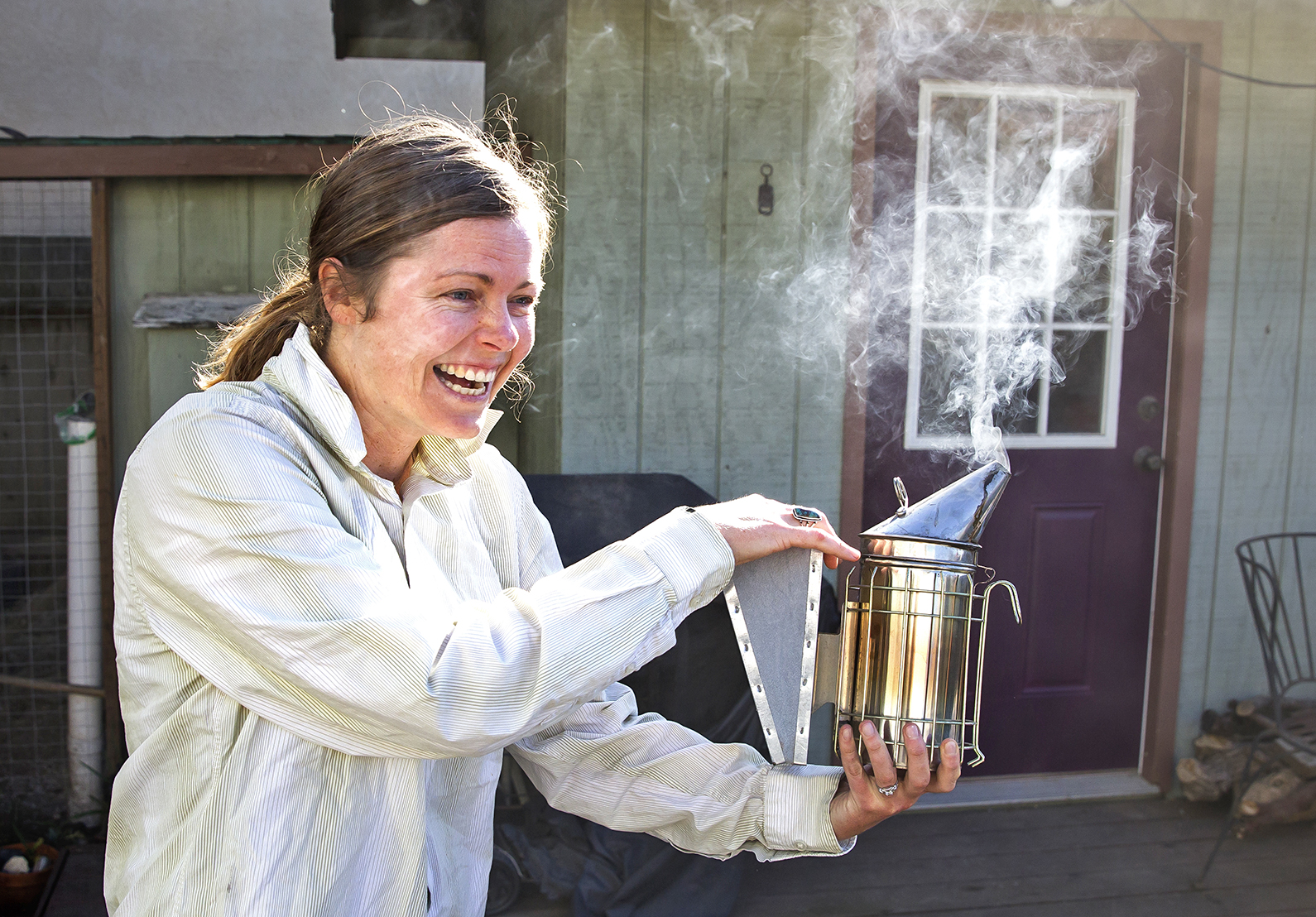 """CAN WE BEE FRIENDS?    A smoker subdues the bees as Lindsey Morgan pulls frames from her single hive located in her Morro Bay backyard. The amateur beekeeper swears the colony mysteriously """"found her.""""    PHOTO BY JAYSON MELLOM"""