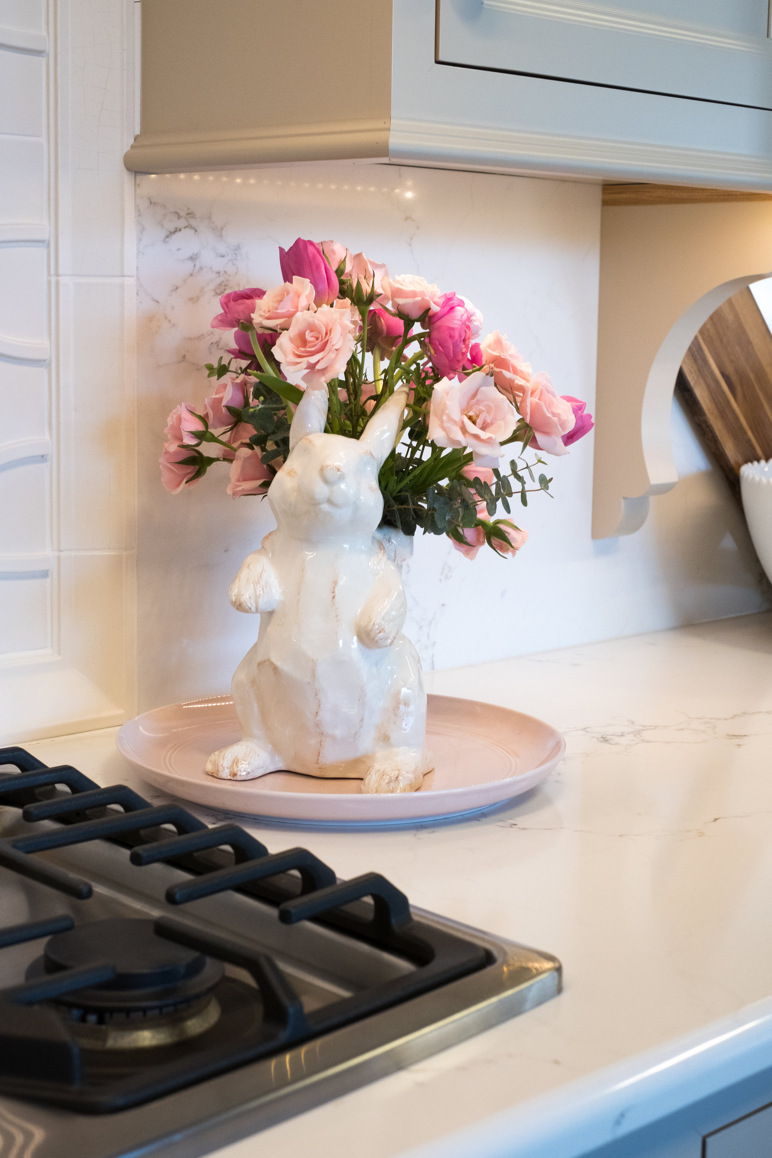 This sweet bunny vase is filled with light pink spray roses, hot pink tulips, hot pink ranunculus and a few sprigs of eucalyptus.