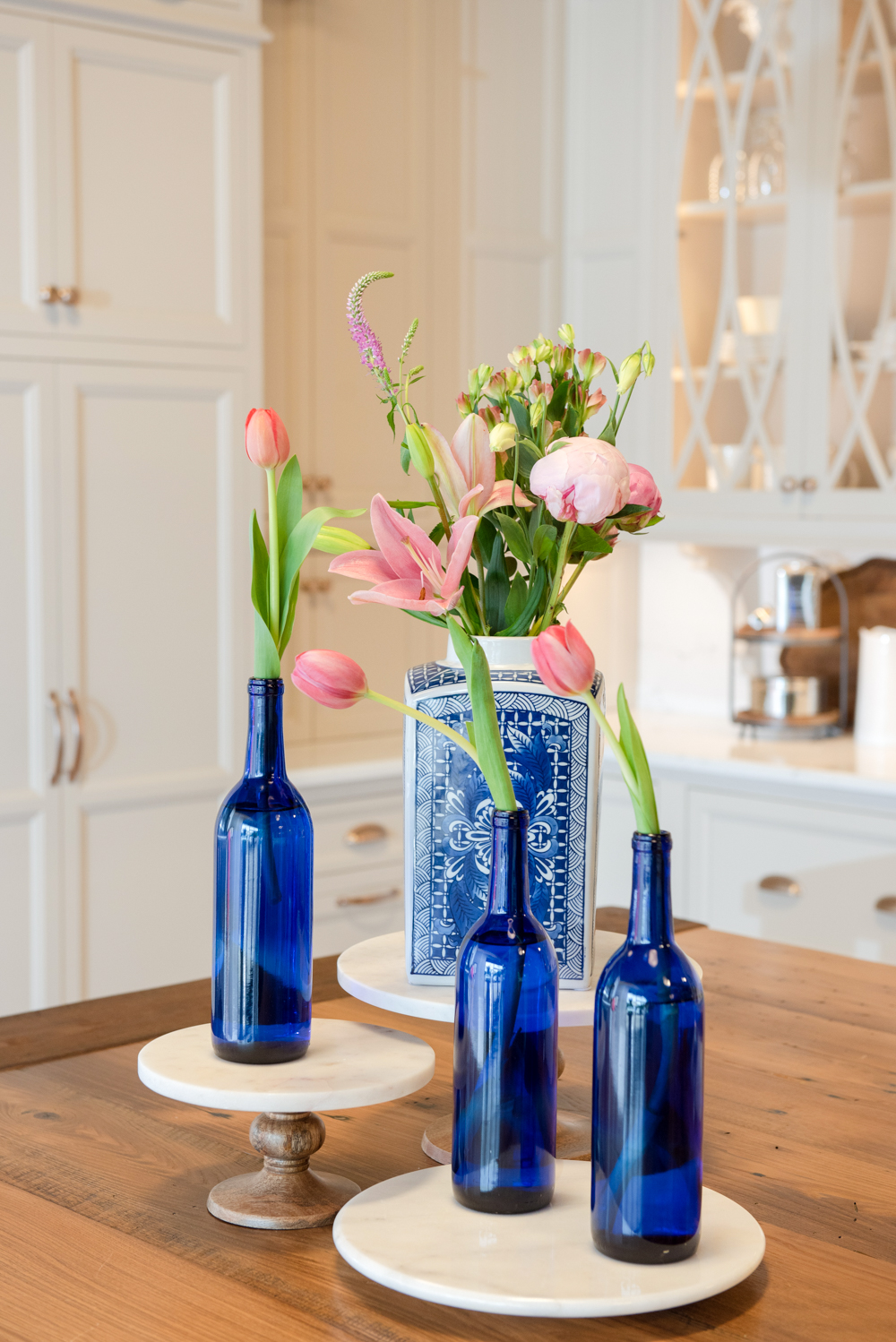 Single stems in blue bottles are just as a stunning as the giant centerpieces and way more time efficient if putting together a party last minute. We used groupings of smaller arrangements to decorate the surfaces around the dining area.
