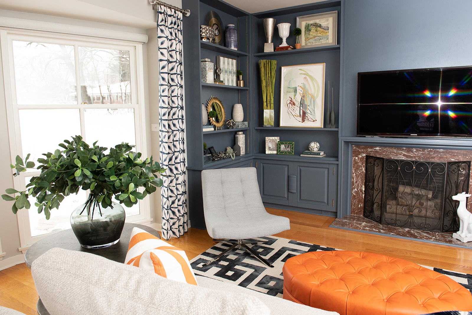 White paint of the windows, a light grey for the walls and a cool, dark blue for the built-ins made the space feel updated, modern and stylish.