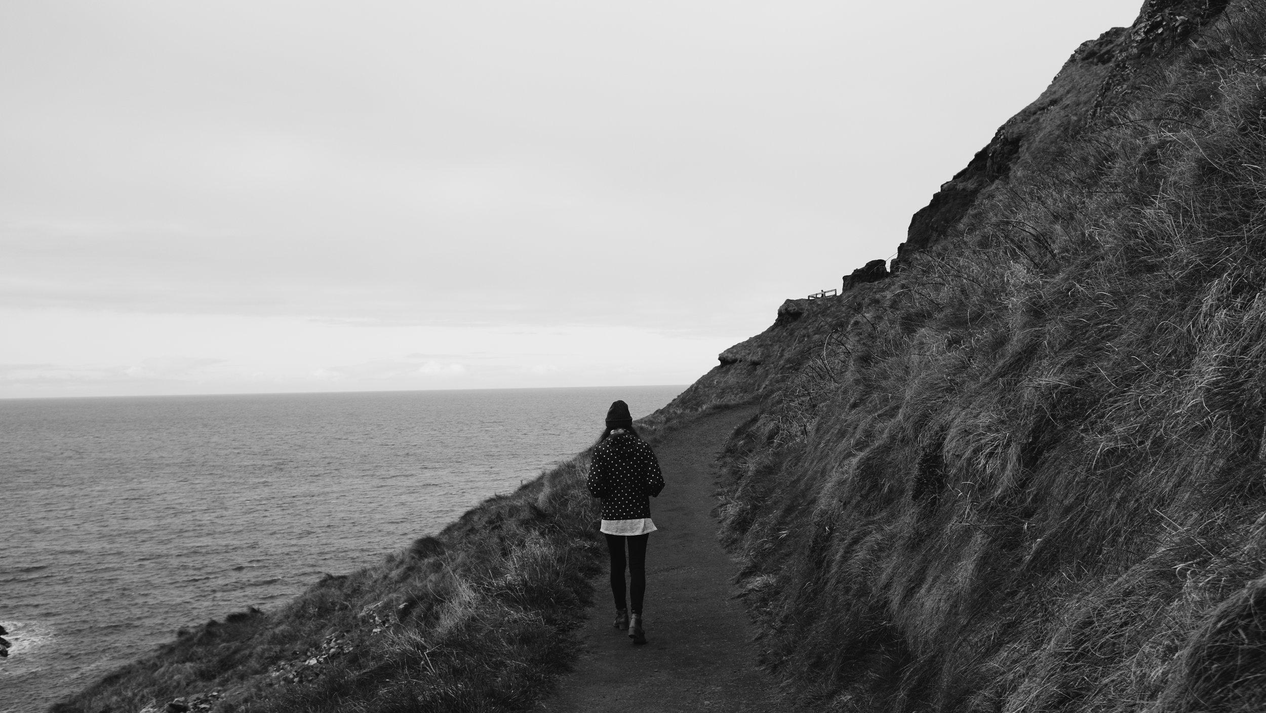 Girl Walking Along the Coast in Ireland by Julia Mary