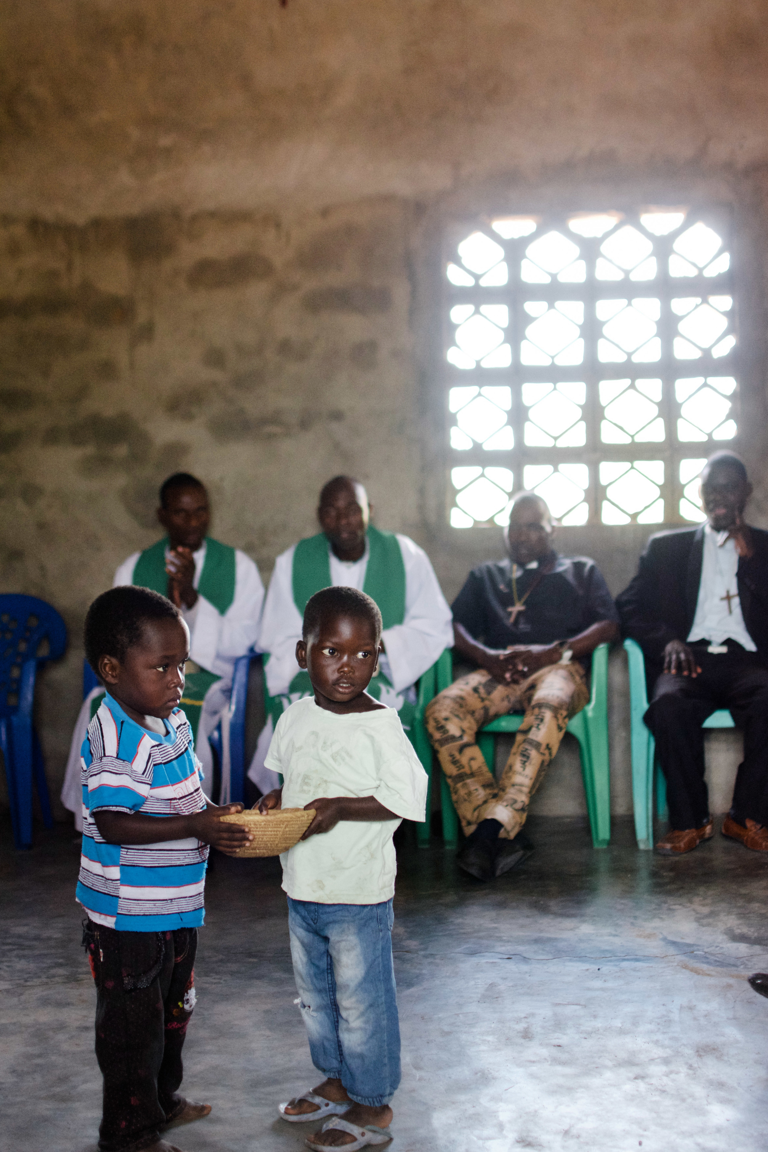 Two young boys collect the offering during a service at São Paulo Lutheran Church in Sena.