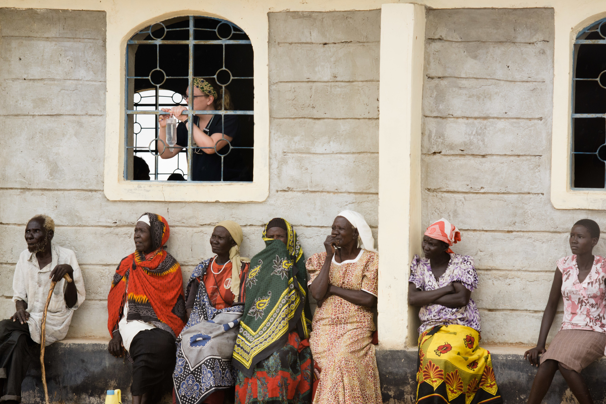 Career missionary Sarah Kanoy hangs an IV bag in the window of the church as patients wait outside.