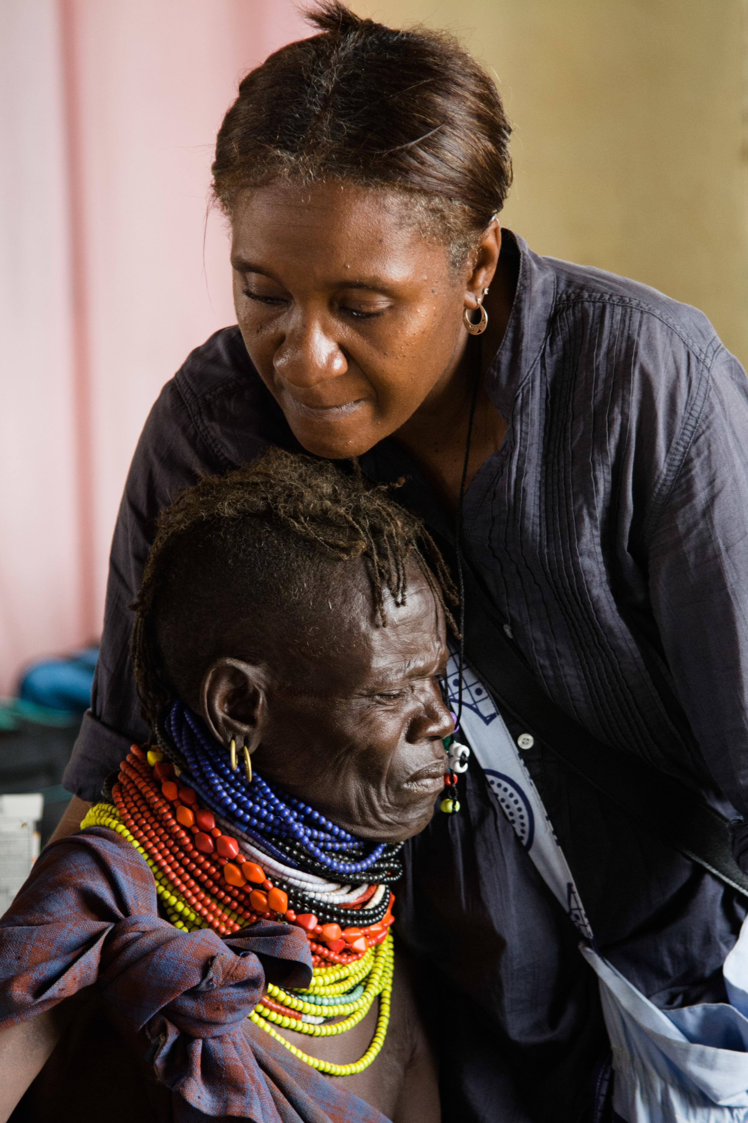 Shara comforting a woman receiving an IV line