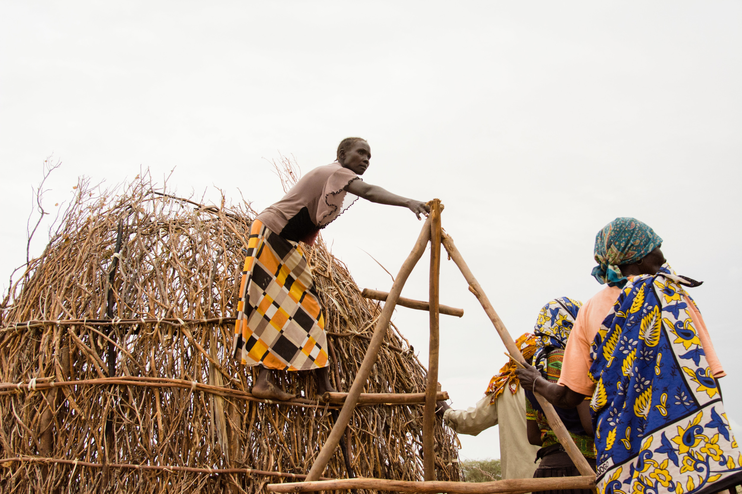 A woman pauses from building a hut to listen to a pastor speak.