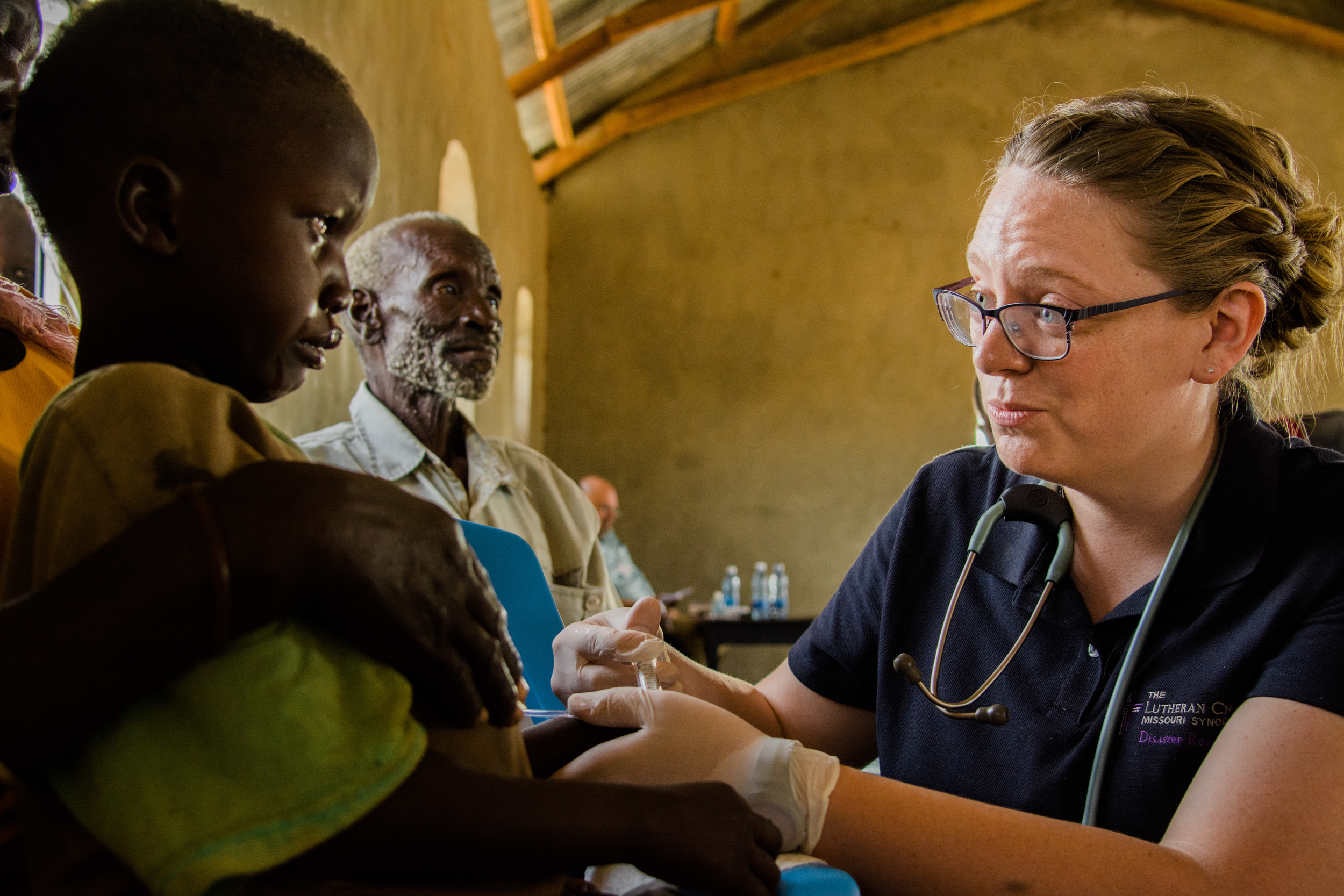 Sarah speaks reassuringly to a little girl receiving IV fluids.