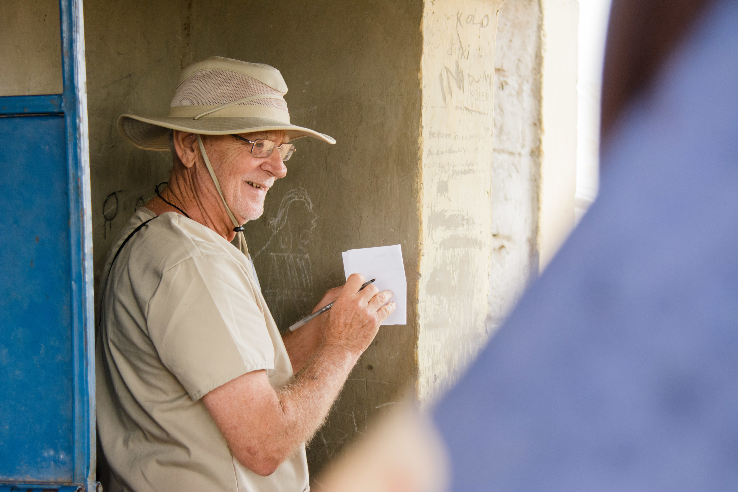 MMT volunteer Brian Lund records the weight of one of the patients.