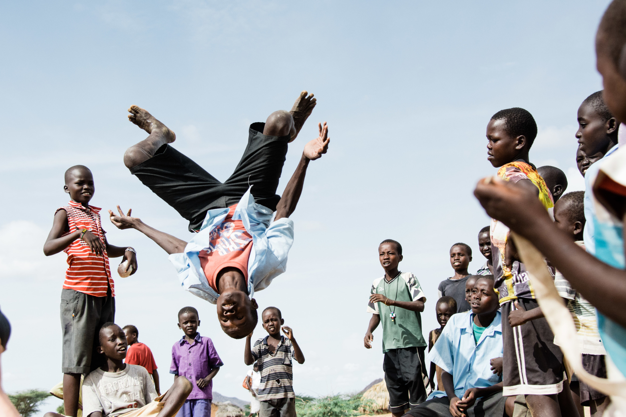Children gathering to watch backflips in the courtyard