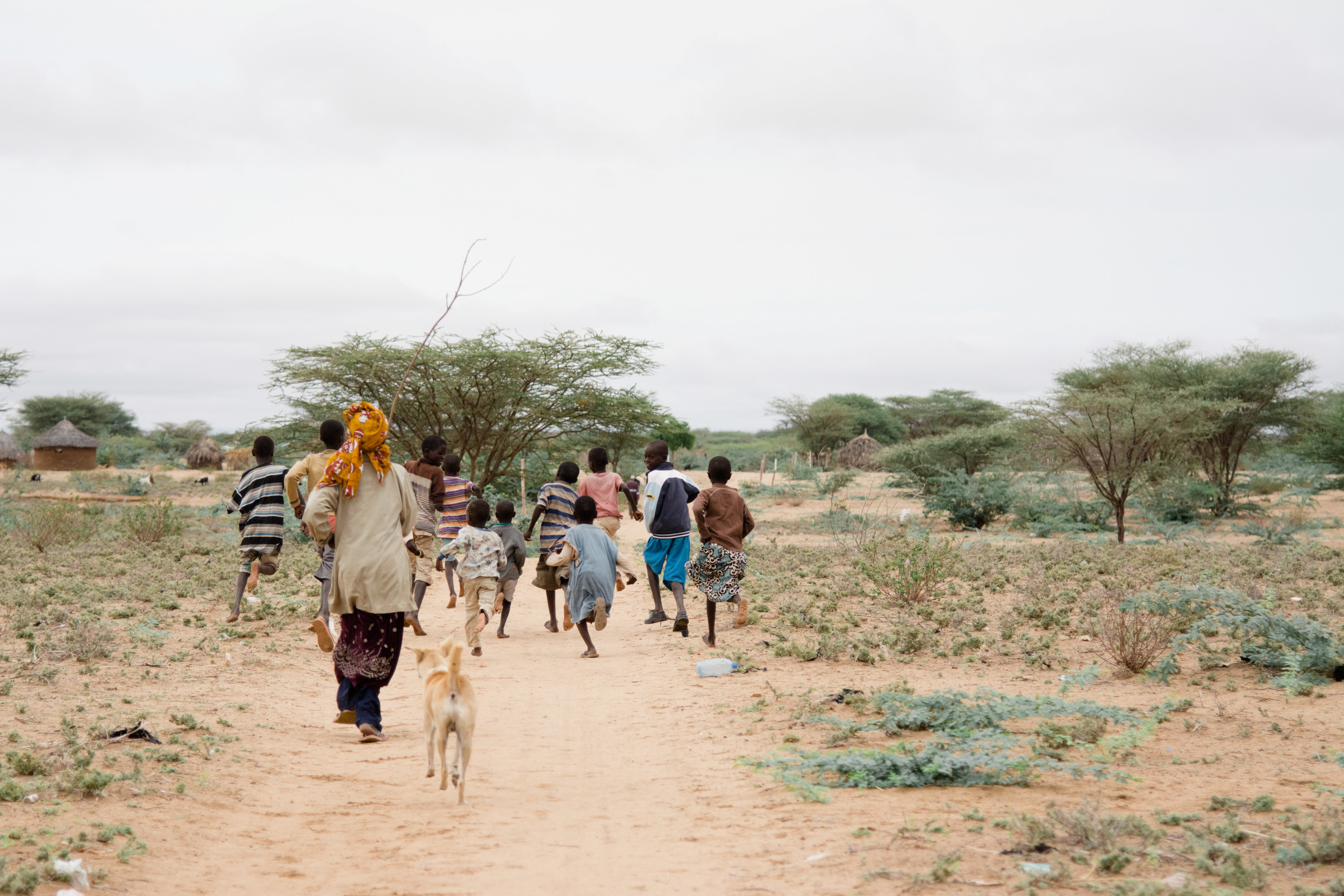 A woman chasing children back to school