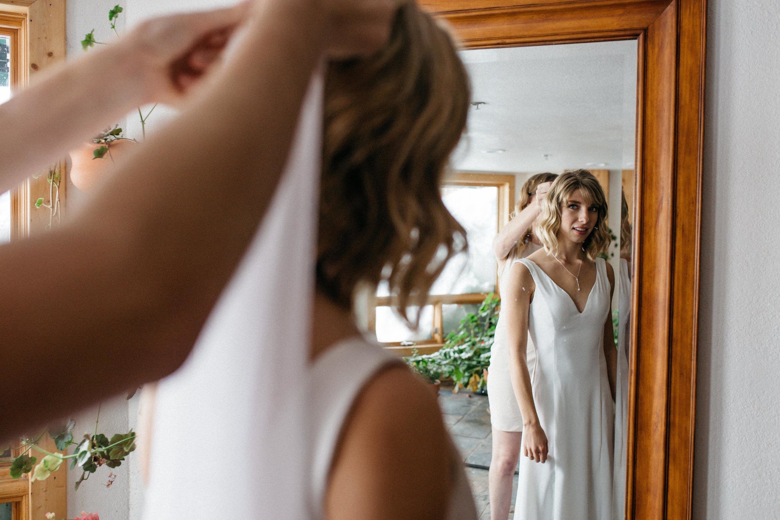 After family portraits and a bit of downtime, I realized the ceremony was a few short minutes away and I had yet to put on my veil. Ellie and I found a quiet spot with a full-length mirror and she fastened on my veil for me. One of the most unplanned, sweetest moments in our friendship, to be sure.