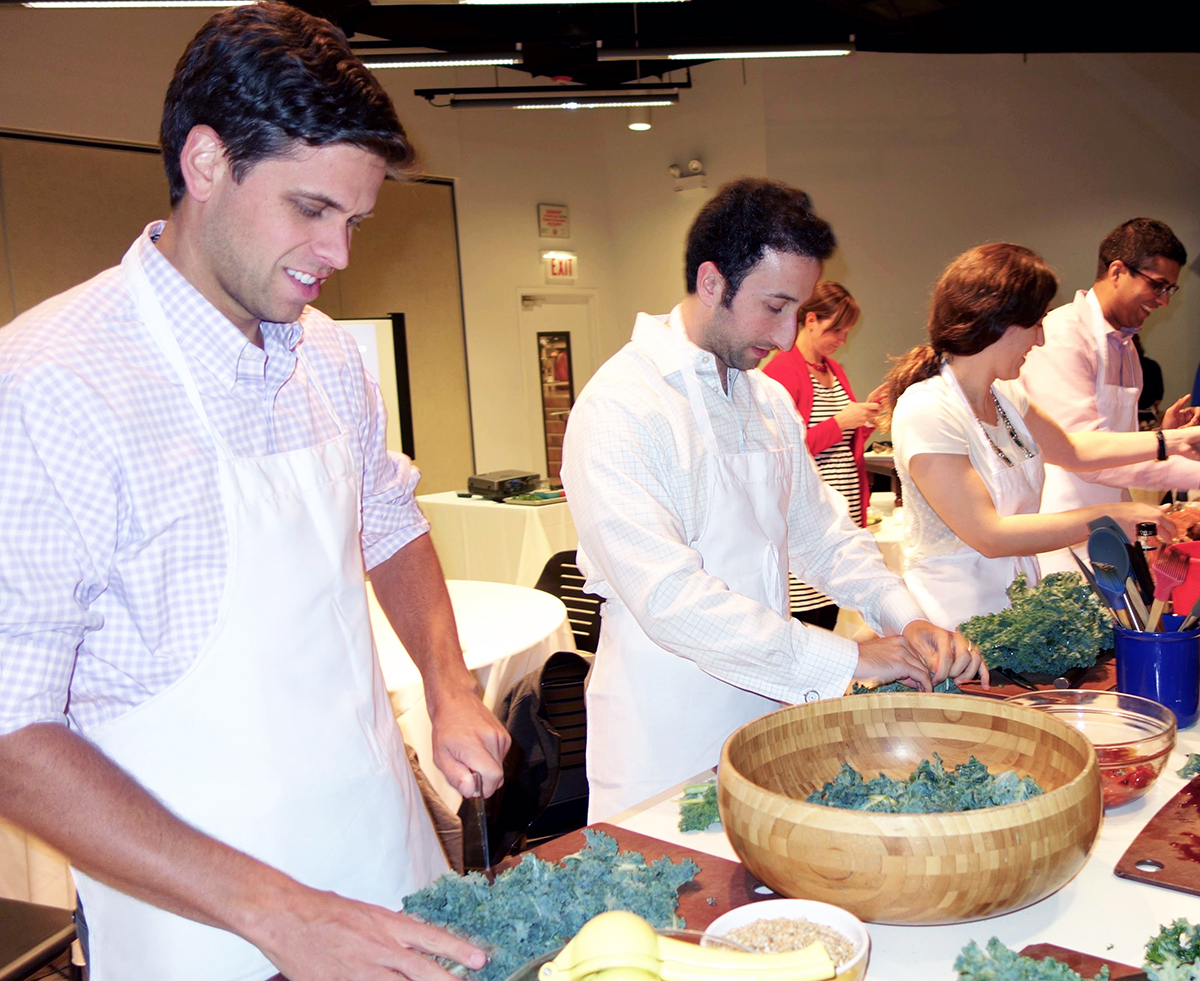 Caridology residents at Cardiology Cooks! chopping and massaging kale for kale salads.