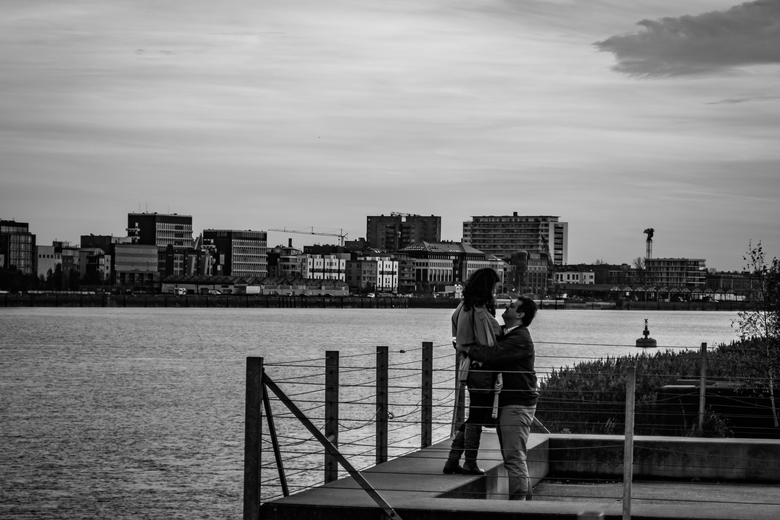 Straatfotografie - Cosmogolem - Linkeroever - Antwerpen. Vanop een afstand zie ik deze man zijn vrouw knuffelen. Ze lachen en teasen elkaar. Lekker ongedwongen. Inbreuk privacy of niet? Wat vind jij?