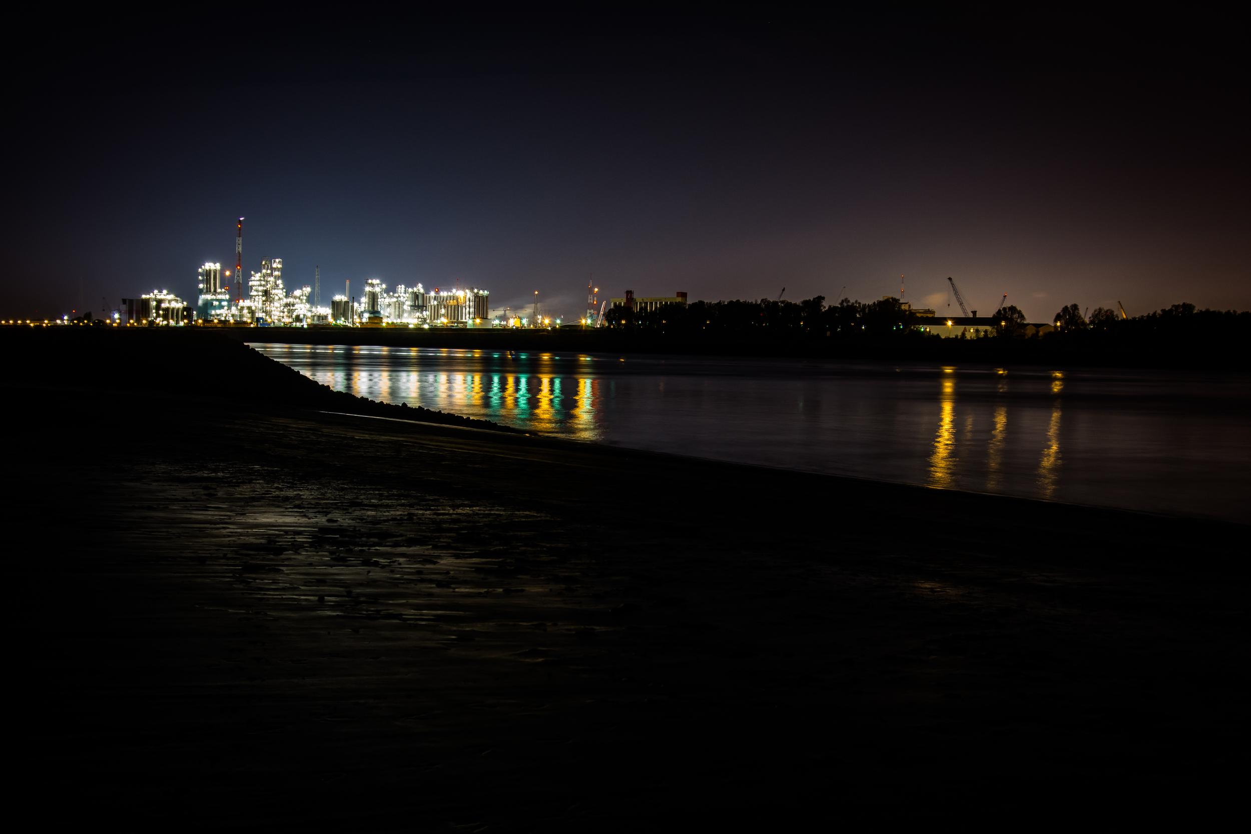 """Plaasj van """"Sintanneke"""". Statief opgesteld. Stukje dijk mee op foto. De lichtjes weerspiegelen. Refelctie in het water fleurt je foto op. Ook nog licht op het zand van het strand."""