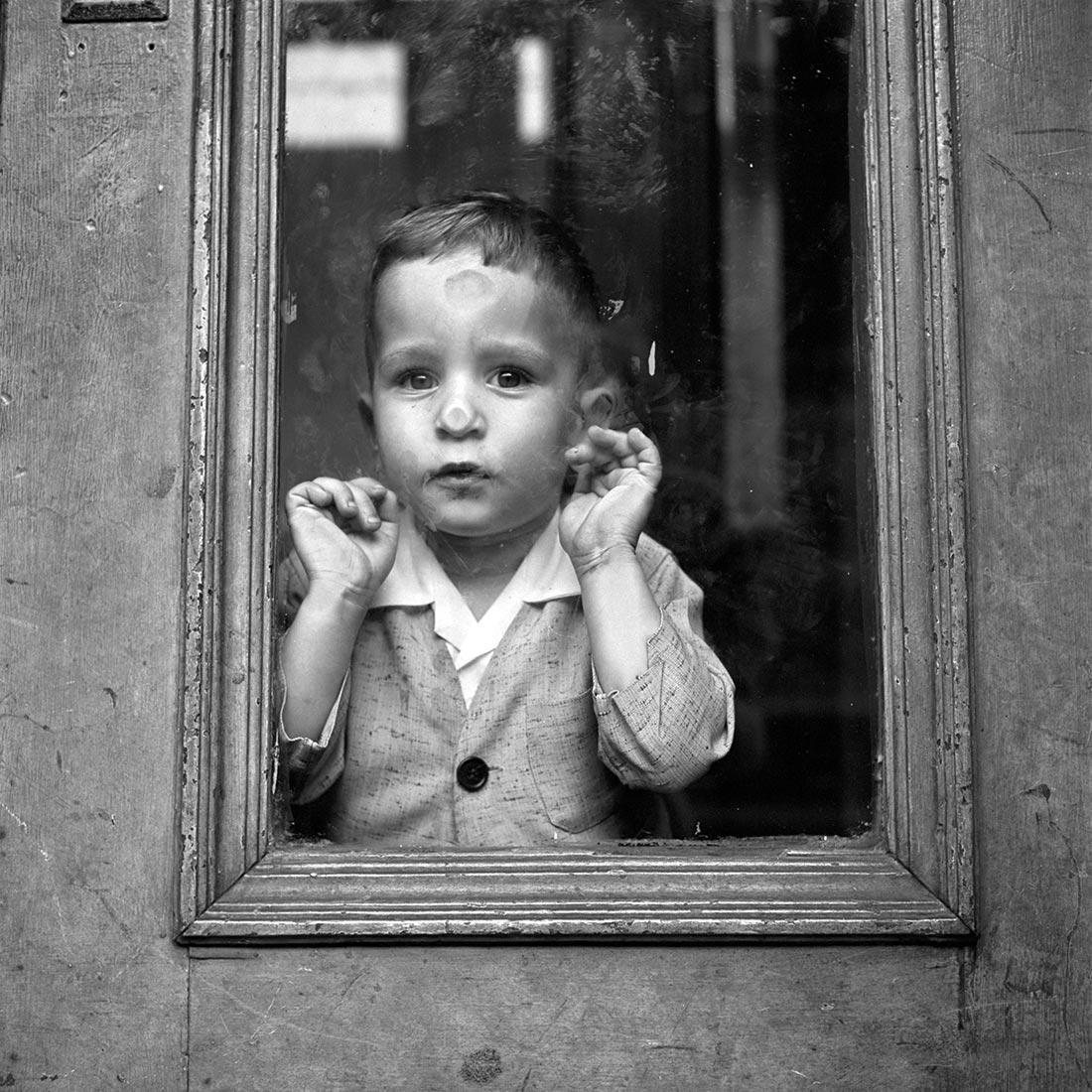 vivian maier jongen met neus gedrukt tegen het raam.jpg