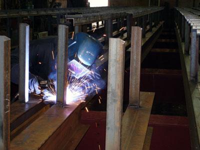Worker welding canopy purlins