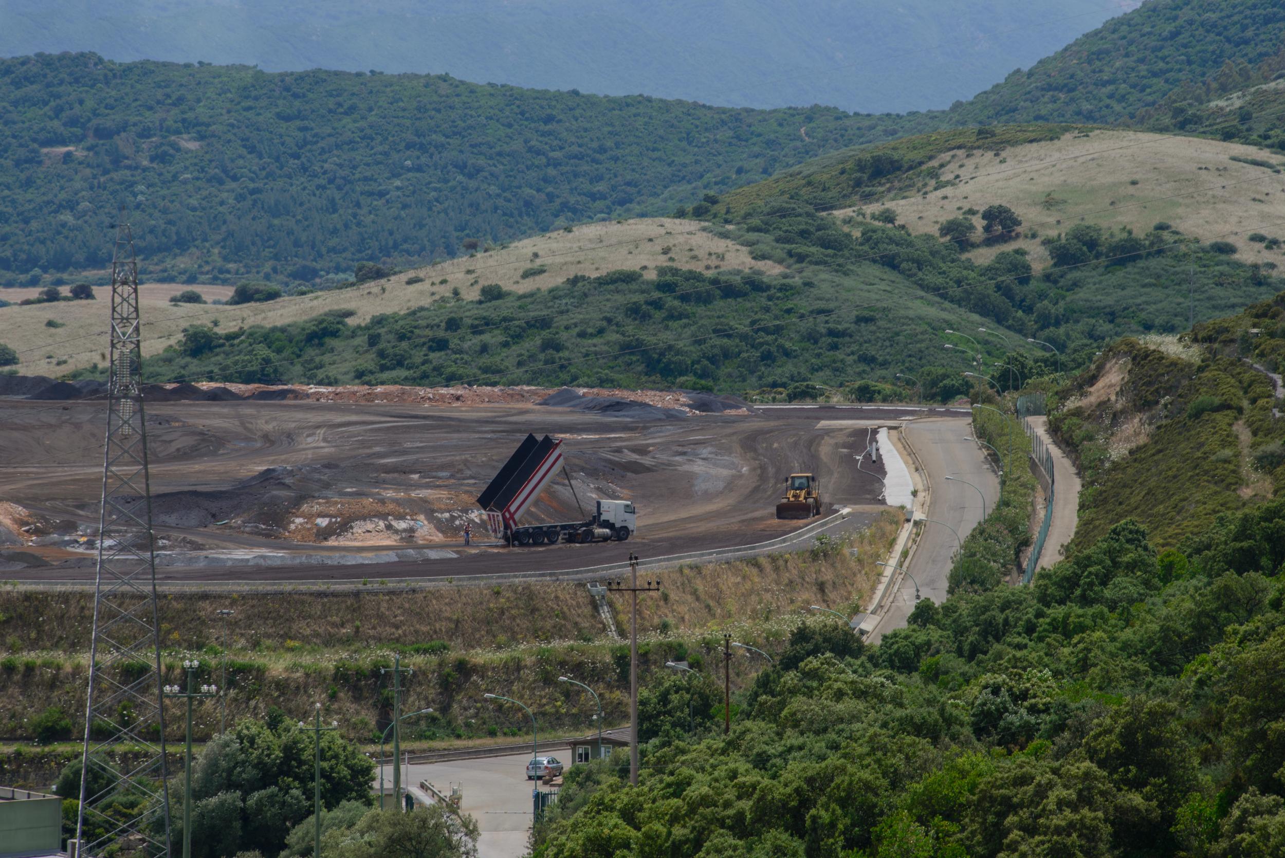 Genna Luas, exminiera estrattiva di zinco e ferronel cuore di selvaggi boschi collinosi e a soli venti chilometridallo stabilimento, èdal 2002 la discarica in cui la Portovesme Srl stocca gli scarti della lavorazione dei fumi di acciaieria.Nel 2012 lo stabilimento diPortovesme ha trattato 215 mila tonnellate di fumi d'acciaieria estraendone zinco, le 100 mila tonnellate di scarti sono stati depositati a Genna Luas. L'incremento produttivo della fabbrica significa aumento di smaltimento delle scorie e quindi la necessaria espansione della discarica.Lo scorso mese di ottobre sono iniziati i lavori di ampliamento della discaricaper la costruzione dell'ottavo argine che saràlungo894 metri,alto 5 echesi poggerà sulle scorie stipatenel settimo anello. Nella delibera n.17/29 del 15/05/2014 della Giunta Regionale è chiaro che conl'ampliamento di Genna Luassi prevedelo smaltimentoquidi nuovi codici CER. Alcuni di questi sono classificati come pericolosi: miscele bituminose, fanghi prodotti dalle operazioni di risanamento delle acque di falda efanghi contenenti sostanze pericolose dal trattamento dei reflui industriali.