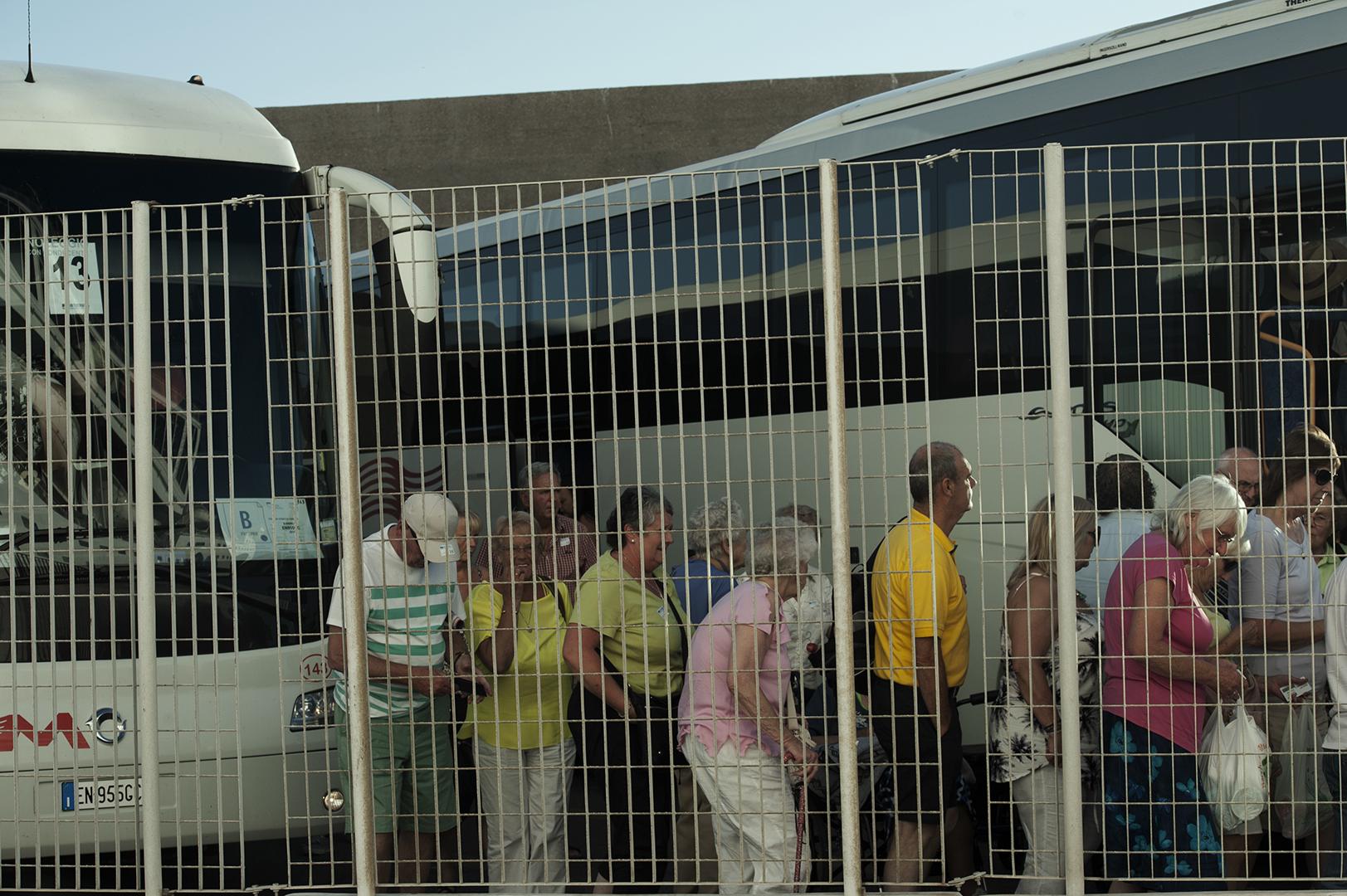 Gruppo di turisti di ritorno dalla visita alla Città Eterna. Il Porto di Civitavecchia è il primo scalo crocieristico del Mediterraneo, con oltre due milioni e mezzo di passeggeri l'anno. Pochi di questi si fermano in città . Di contro si verifica spesso un vero e proprio assalto a pullman e treni per visitare Roma o la vicina Toscana. Civitavecchia, 2014. (Patrizia Pace)