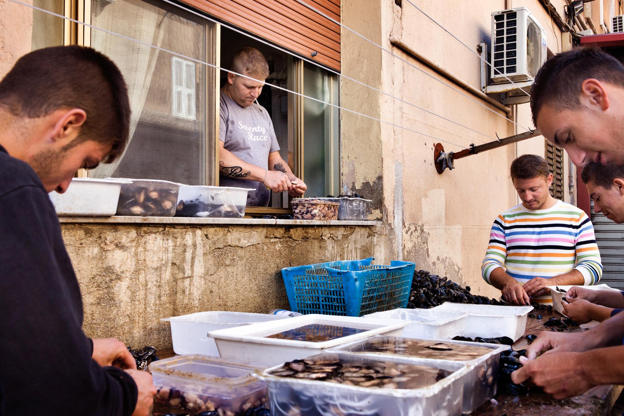 Taranto, Italia, 26 Settembre 2013. Armando e i suoi amici puliscono le cozze nella Città Vecchia. Armando è agli arresti domiciliari, per questo motivo lavora dalla finestra di casa. Nel 2012, a causa dell'alta concentrazione di diossina e Pcb rilevata dalla Asl di Taranto, sono state fatte distruggere circa 20 mila tonnellate di cozze (metà della produzione complessiva). Attualmente è vietata la coltura dei mitili nel primo seno del Mar Piccolo. In questo modo si perdono quelle caratteristiche ambientali che fornivano alle cozze e ostriche tarantine la loro unicità.