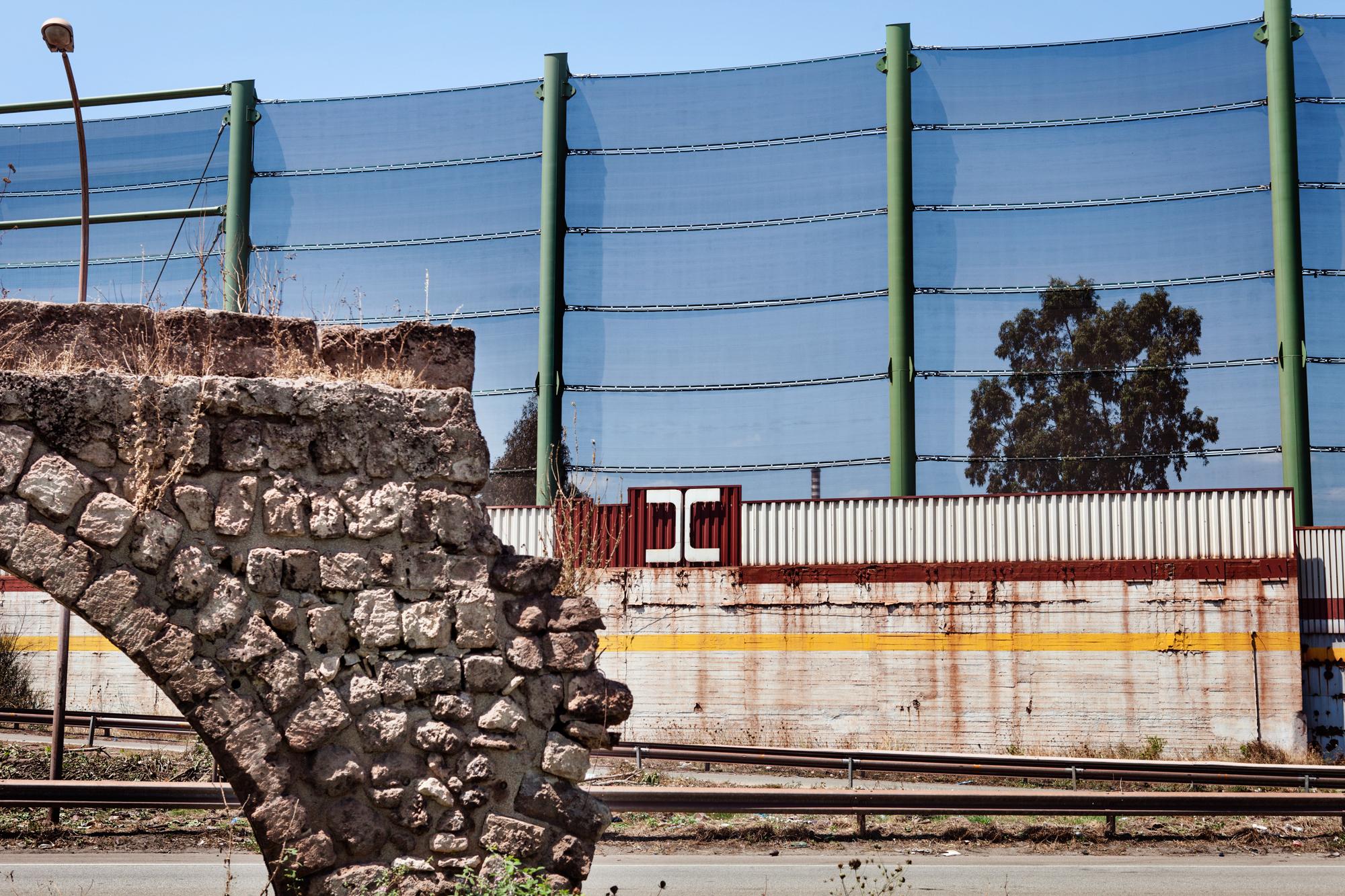 Taranto, Italia, 1 Agosto 2013. Recinzione dello stabilimento Ilva di Taranto. La rete sopra alle mura è stata costruita nel 2012 come previsto dall'Aia (Autorizzazione Integrata Ambientale rilasciata dal Ministero dell'Ambiente) per difendere l'adiacente quartiere dei Tamburi dalla diffusione delle polveri di minerali provenienti dall'impianto. In primo piano, i resti dell'acquedotto del Triglio, di epoca romana. Tamburi deve il proprio nome al rumore delle gocce di acqua che cadevano dall'acquedotto, simile al suono delle percussioni.