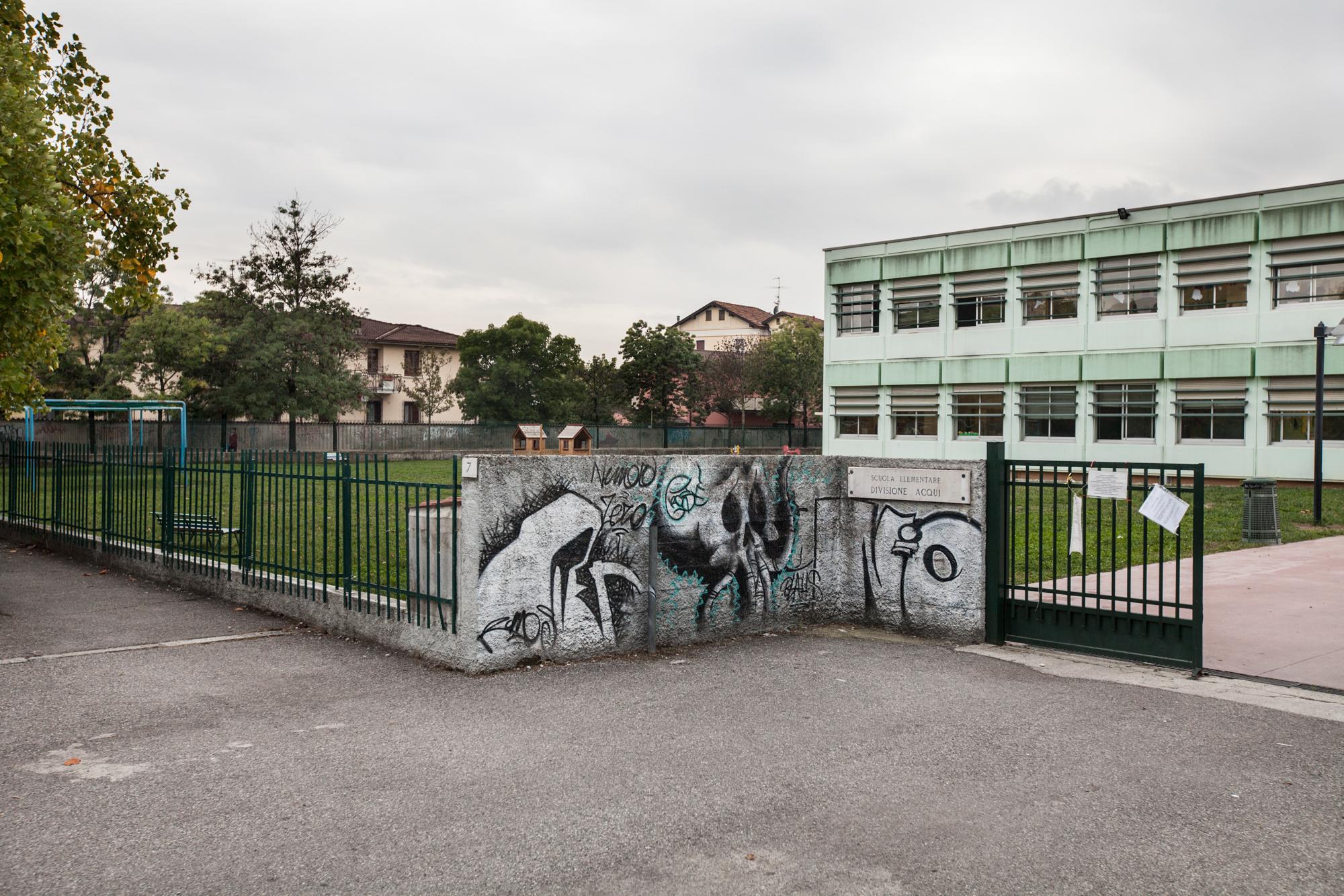 La scuola elementare Divisione Aqui. Il giardino è stato bonificato, ma il terreno esportato, è stato poi utilizzato nella costruzione delle colline del nuovo sbocco della tangenziale, due chilometri più' a est. Brescia / Italia. Ottobre 2013