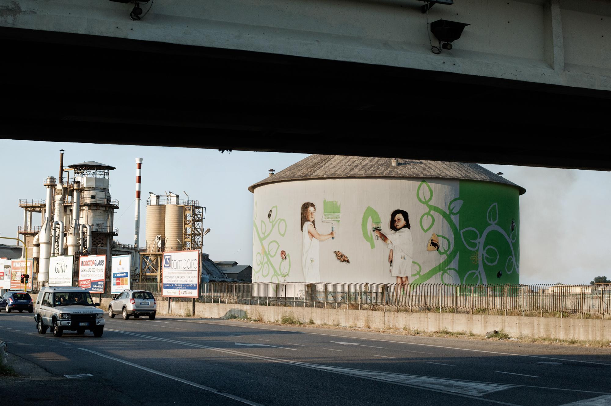 Italia. Crotone 2013: Il silos della Pertusola Sud coperto da un murales commissionato dall'Eni, che dirige la bonifica della zona industriale.