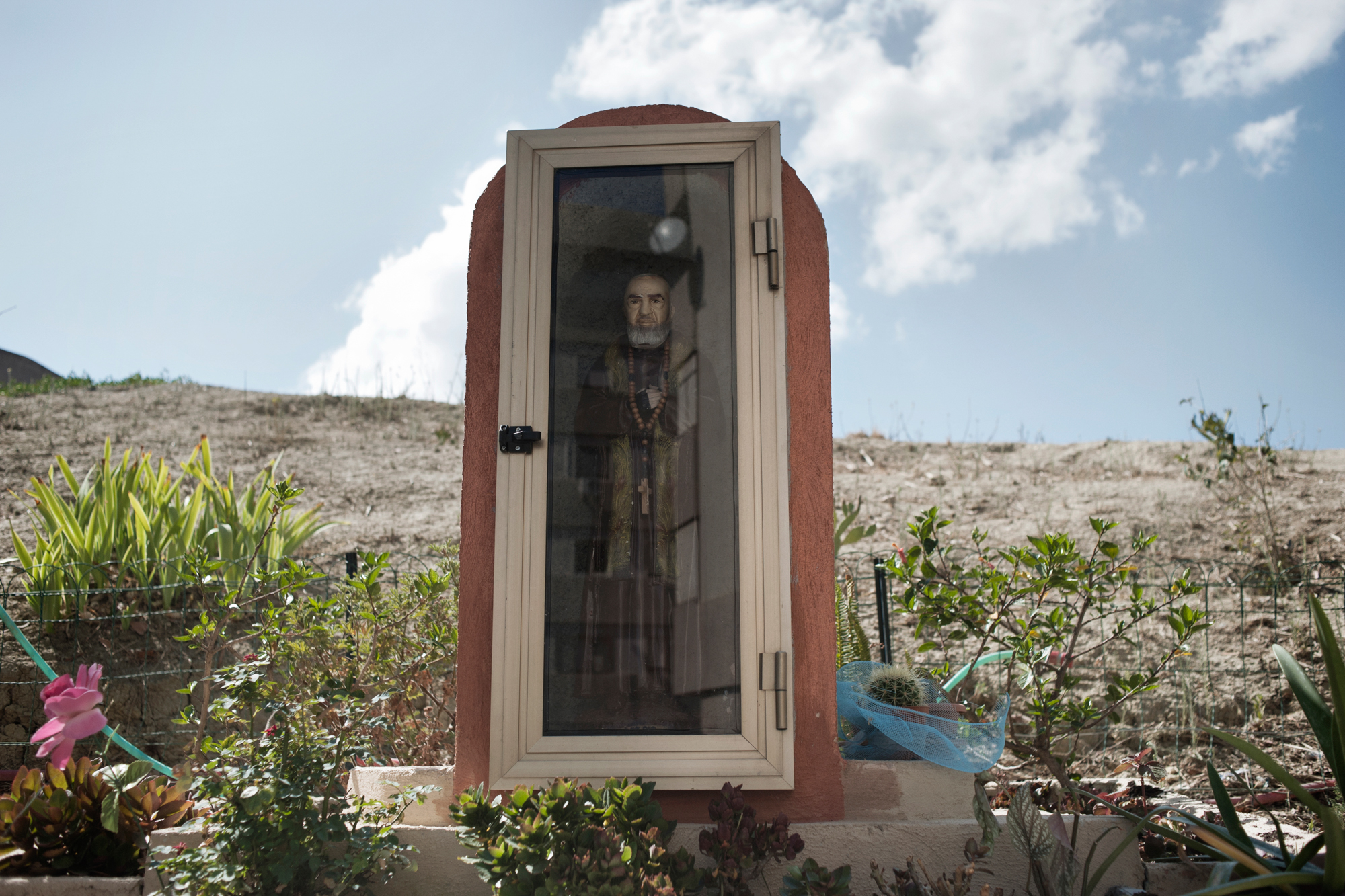 Italia. Crotone 2013: Un'icona di Padre Pio nel vecchio quartiere operaio.