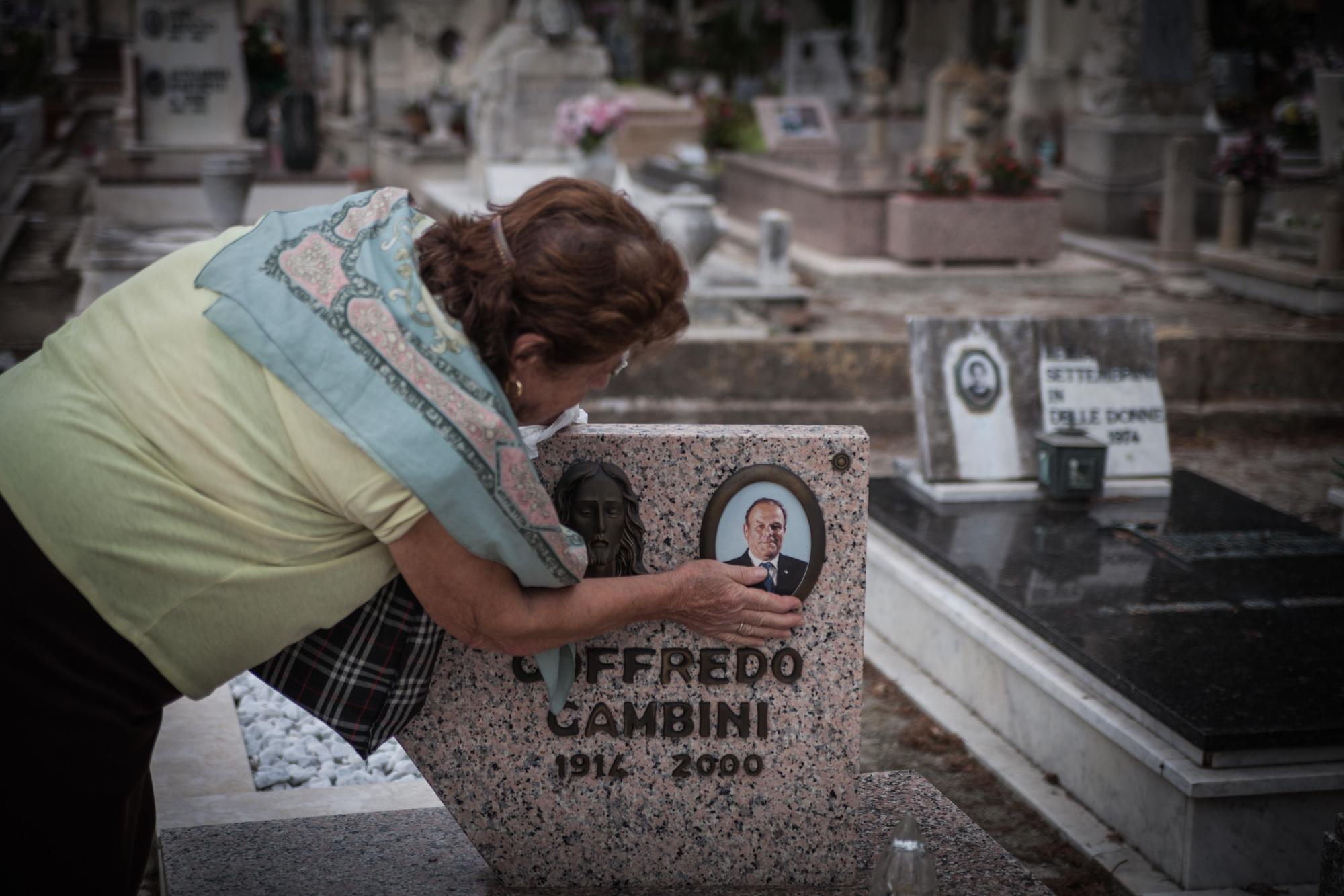 Elisa Gambini sulla tomba del padre, ex dipendente S.I.To.Co. cimitero di Orbetello (Grosseto), 2015.Il figlio di Elisa, Giorgio, si è ammalato di tumore ai polmoni e dopo quattro anni di cure è morto di infarto nel gennaio 2015 a 50 anni. Oggi la fabbrica è ricoperta di circa 28.000 metri quadri di lastre di amianto, completamente deteriorate.