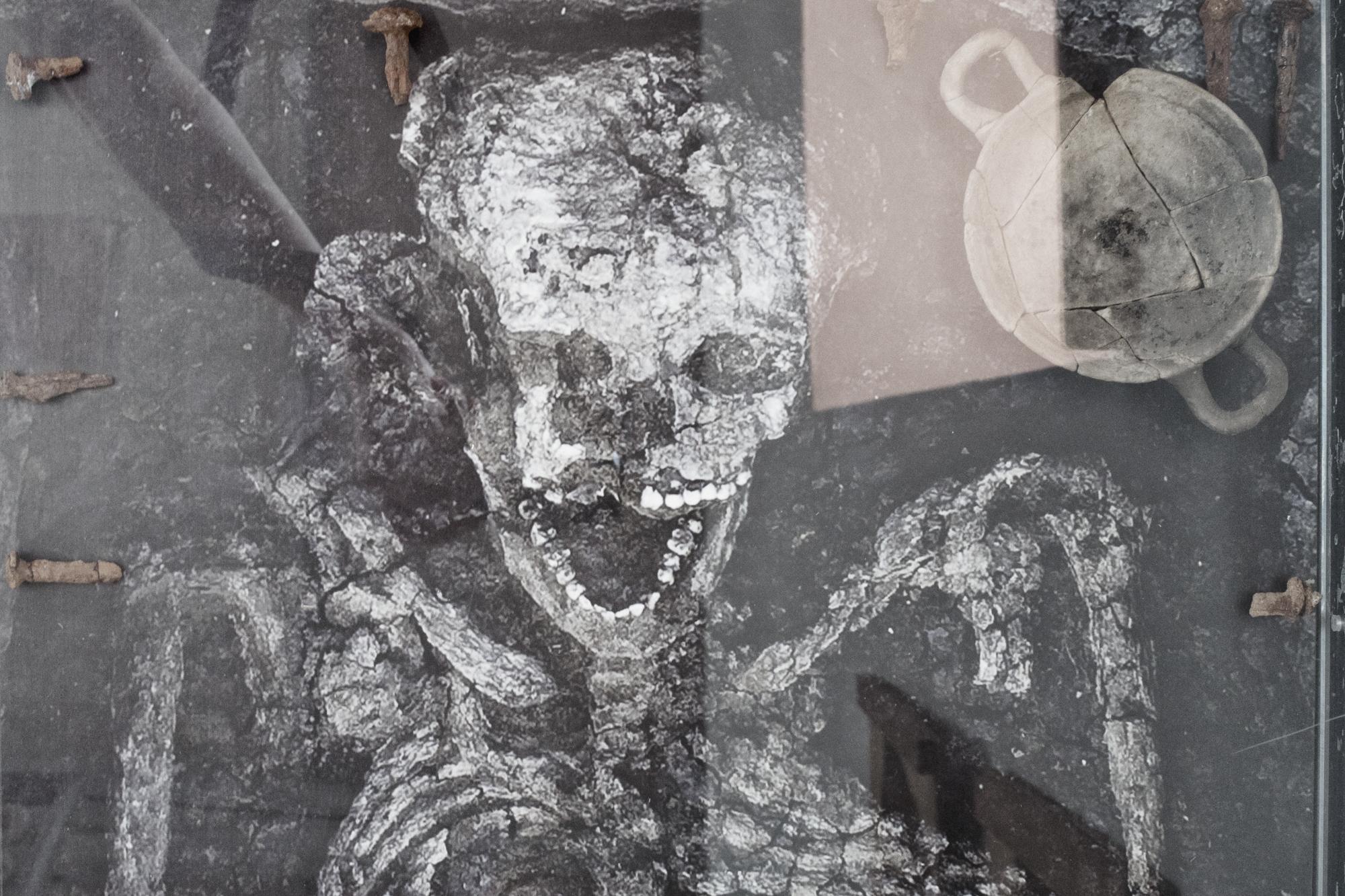 Dettaglio di sepoltura, dal Museo Archeologico di  Satricum . Le Ferriere (LT), 2015.  Intorno al nucleo centrale della città di  Satricum  sono state scoperte diverse necropoli. Nel museo accanto al sito archeologico sono esposti alcuni degli scheletri ritrovati, tra cui quello di un uomo tra i 25 e i 30 anni, risalente al V secolo A.C.
