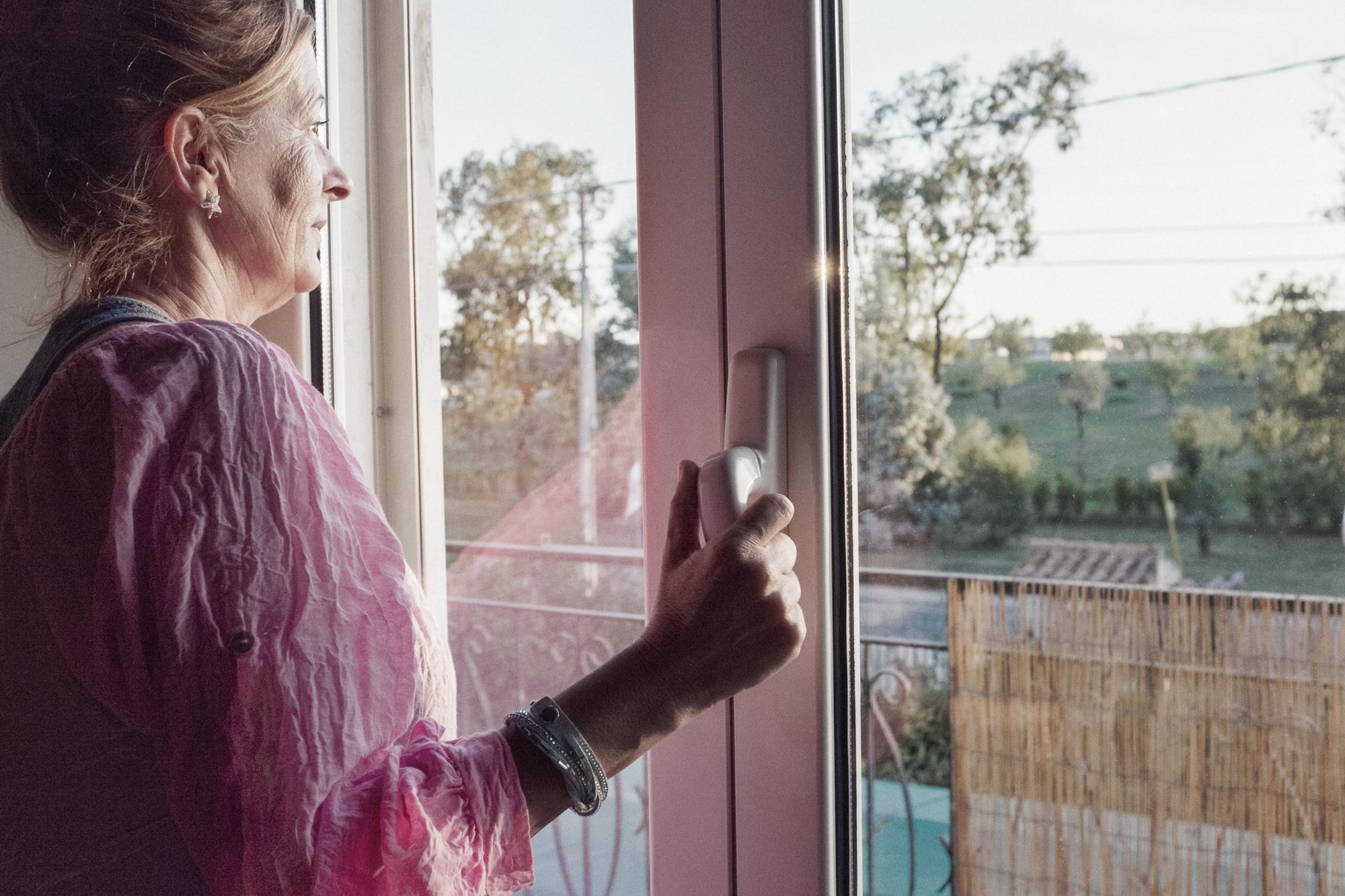 Carla Piovesan, 56 anni, nella sua abitazione di fronte alla discarica di Borgo Montello (LT), 2015.  Carla abita qui da quando è nata ed è sempre costretta a serrare tutte le finestre per bloccare i miasmi causati dalla discarica. Il bacino di raccolta rifiuti dista solo 150 metri dalla sua abitazione, invece dei 700 metri imposti dalla Delibera Consiglio Regionale n°112 del 10 luglio 2002. Il padre era uno degli emigrati veneti degli anni Trenta ed è morto di tumore nel 2009, come tanti altri residenti della zona. Carla ancora ricorda come, negli anni di mala gestione dell'impianto, il padre pulisse la strada nei pressi del loro cancello dai cumuli di percolato rilasciati dai camion diretti alla discarica.