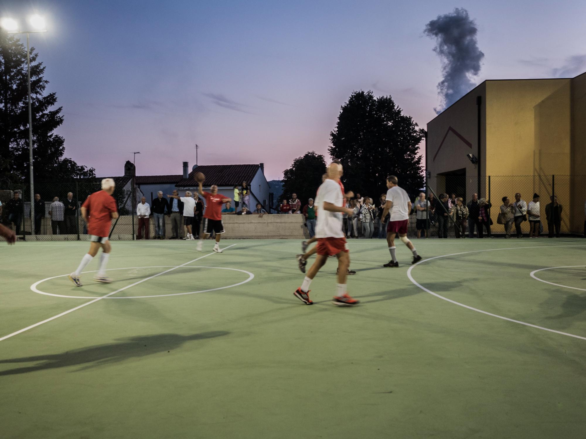 """Partita amichevole nel nuovissimo campo di pallacanestro all'aperto nel rione Servola di Trieste, alle spalle una delle """"fumate nere"""" dell'adiacente Ferriera.Trieste, 2015."""