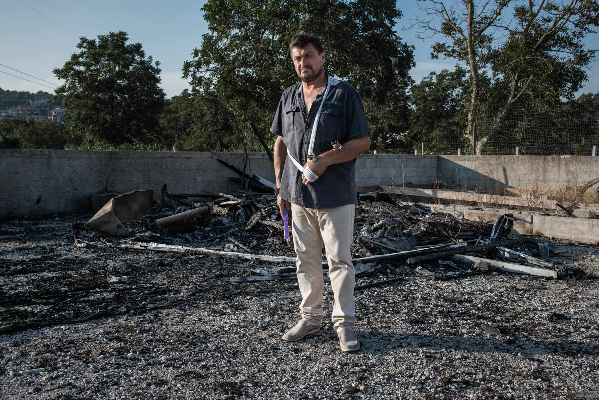 Pianura, (NA), 2015. Vincenzo Russo, membro dell'associazione  Rinascita dei Campi Flegrei  e militante del movimento 5 Stelle davanti alla propria roulotte bruciata, un avvertimento per la sua opposizione alla Camorra.