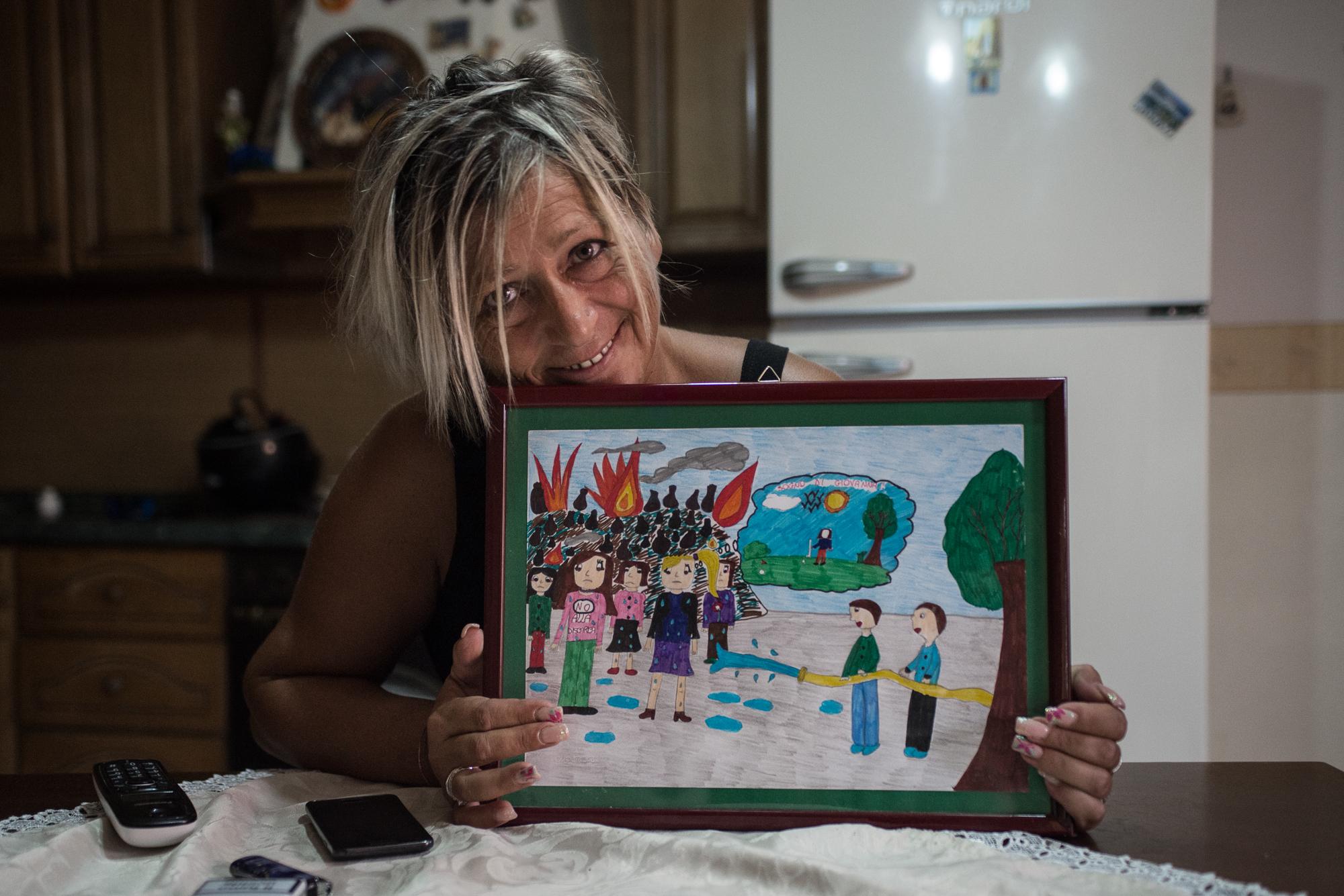 Pianura, (NA), 2015. Giovanna, 45 anni, residente a Napoli, nel quartiere di Pianura. Reduce da diverse patologie tumorali sconfitte e con altre patologie in via di sviluppo, mostra un disegno degli alunni della scuola elementare in cui ha lavorato.