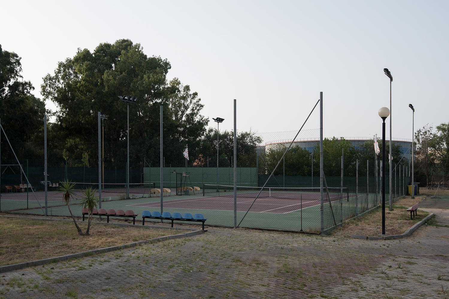 Palestre e campi sportivi sorgono a ridosso di imponenti cisterne disposte lungo i confini della raffineria. Sarroch (Cagliari), 2017