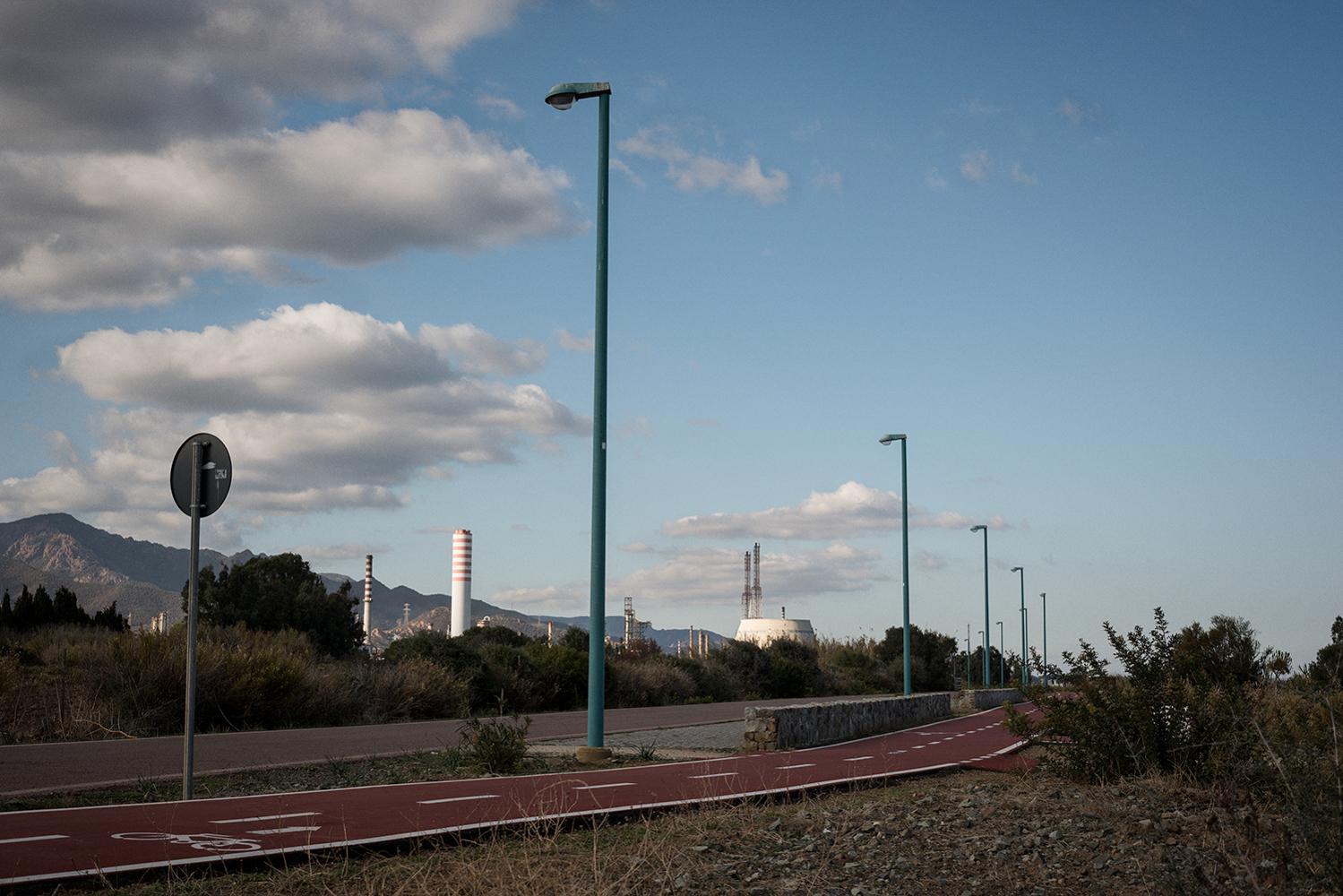 D'estate, a fine giornata, gli abitanti di Sarroch si rilassano praticando sport lungo il litorale che lambisce il parco di Sa Punta. L'area verde, da tempo chiusa al pubblico, si trova in prossimità di una discarica sotterrata a pochi metri dall'industria. Sarroch (Cagliari), 2017.