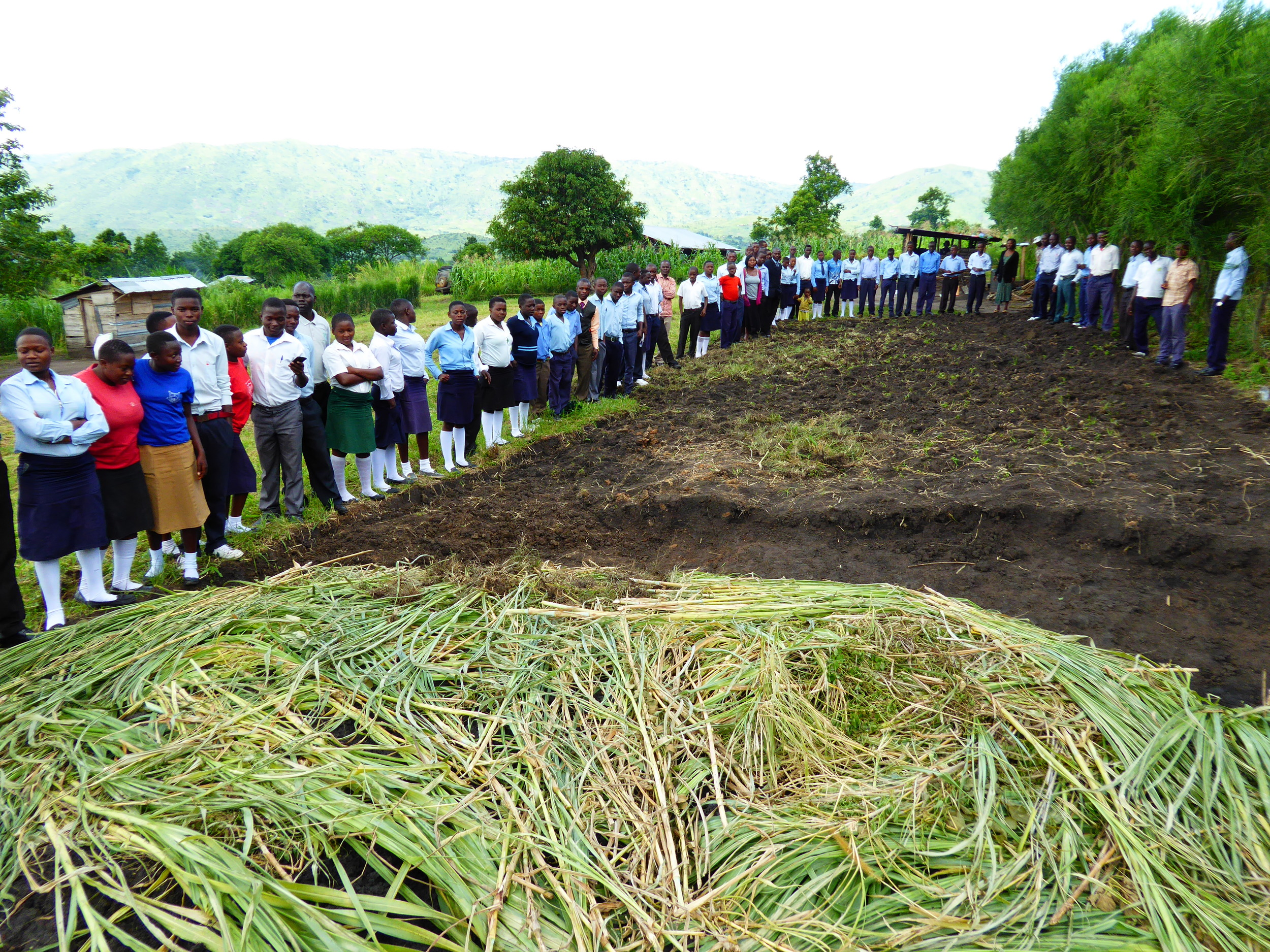 Students standing around land where permanent classrooms will be built