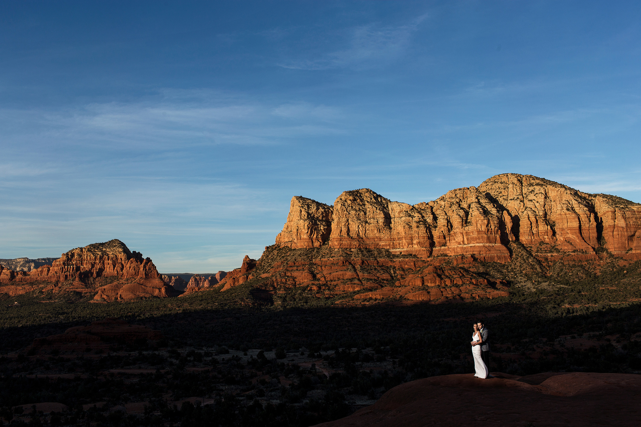 bride and groom sunset portrait with sandstone formations of Sedona Arizona in the background