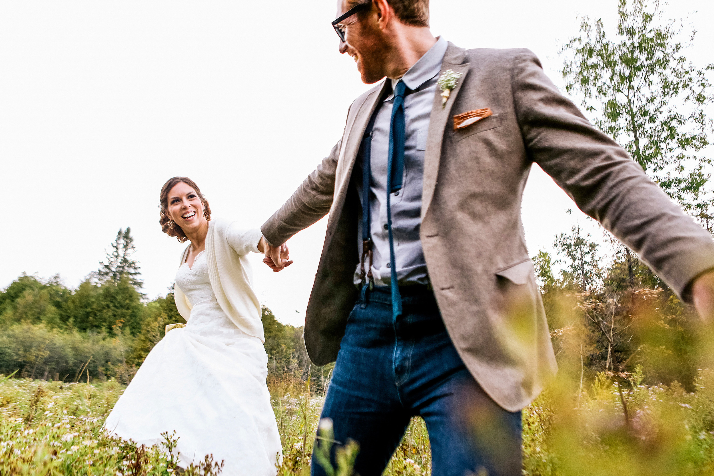 Bride and groom running hand in hand though a field at a Herb Garden wedding in Almonte Ontario