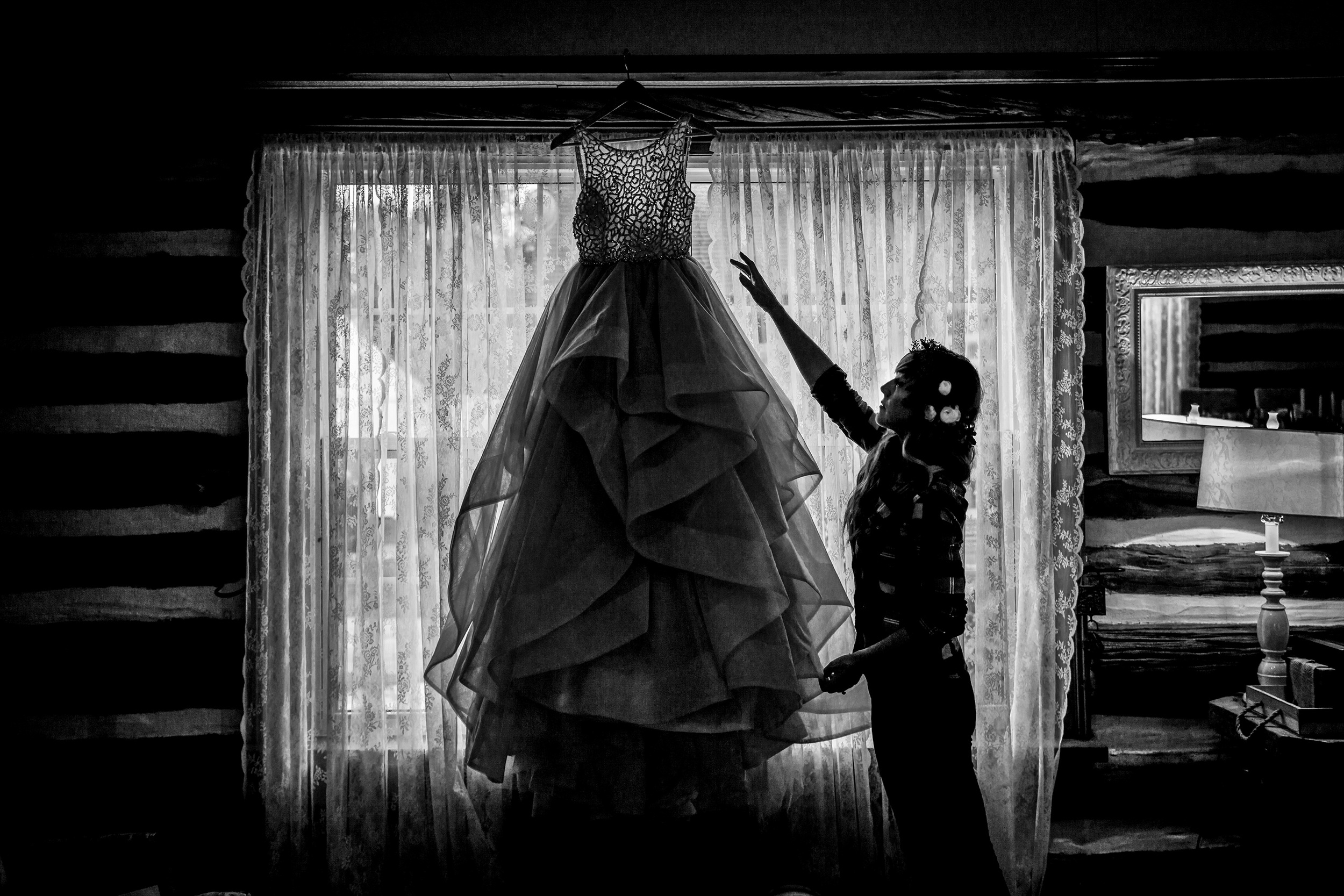 bride retreives wedding dress that is hung in the window at a stonefields wedding in carelton place ontario