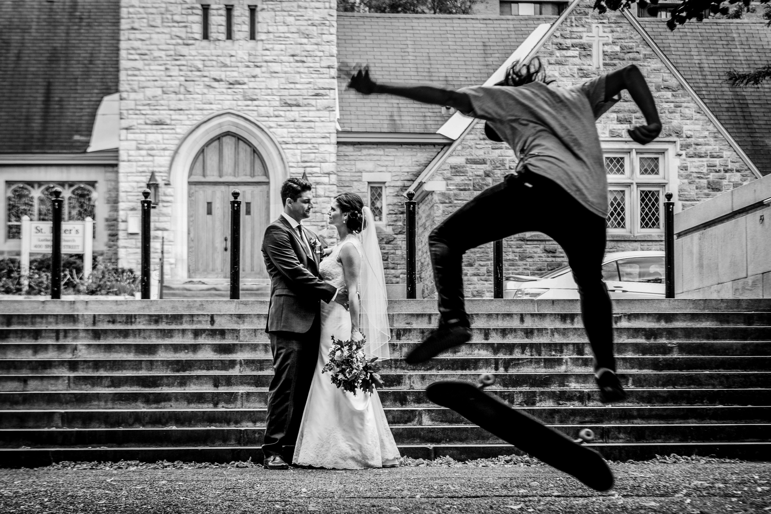 Photograph of a bride and groom with a skateboarder passing by