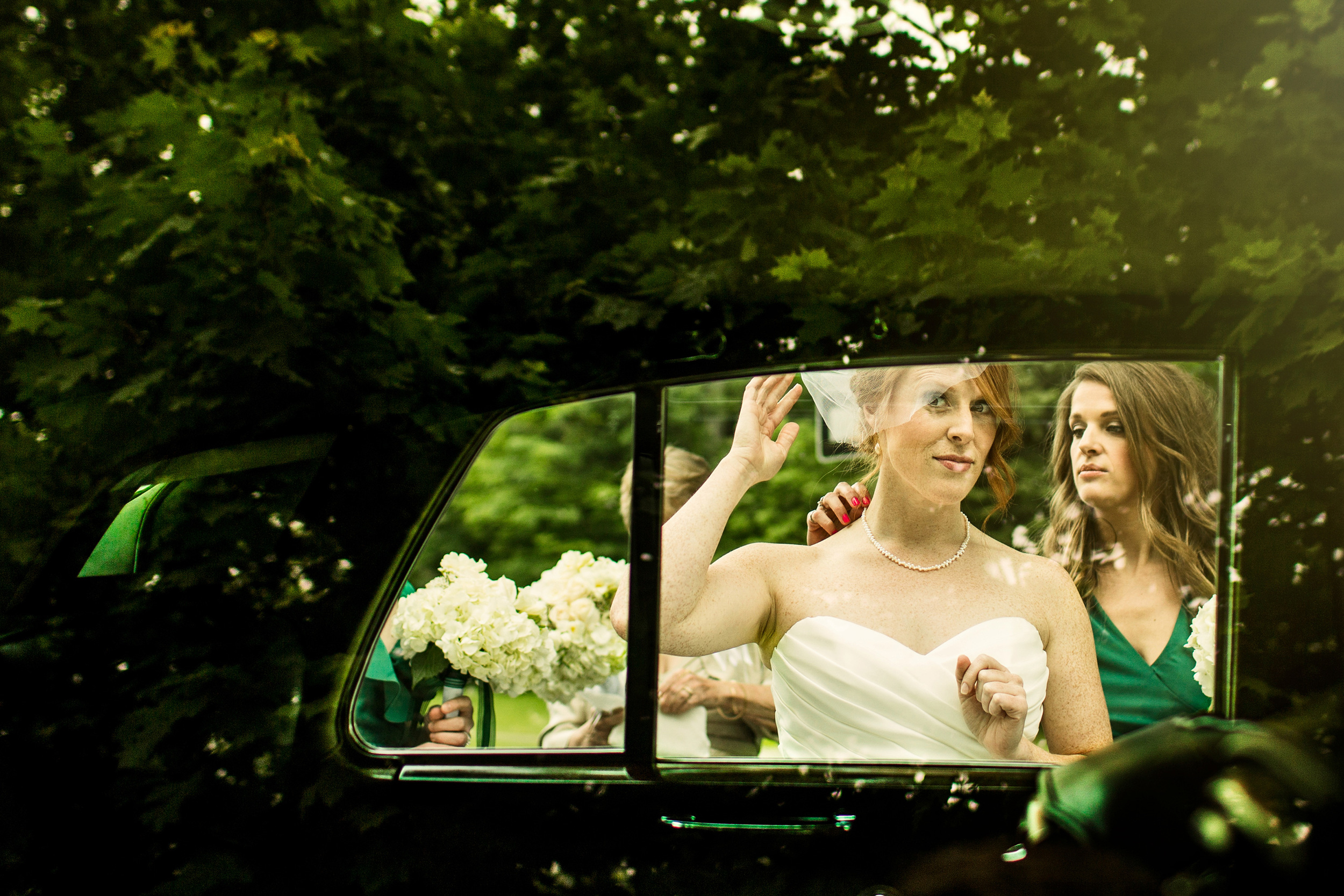 bride adjusts hair in the reflection of a limo window before a rockcliffe park pavilion wedding ceremony