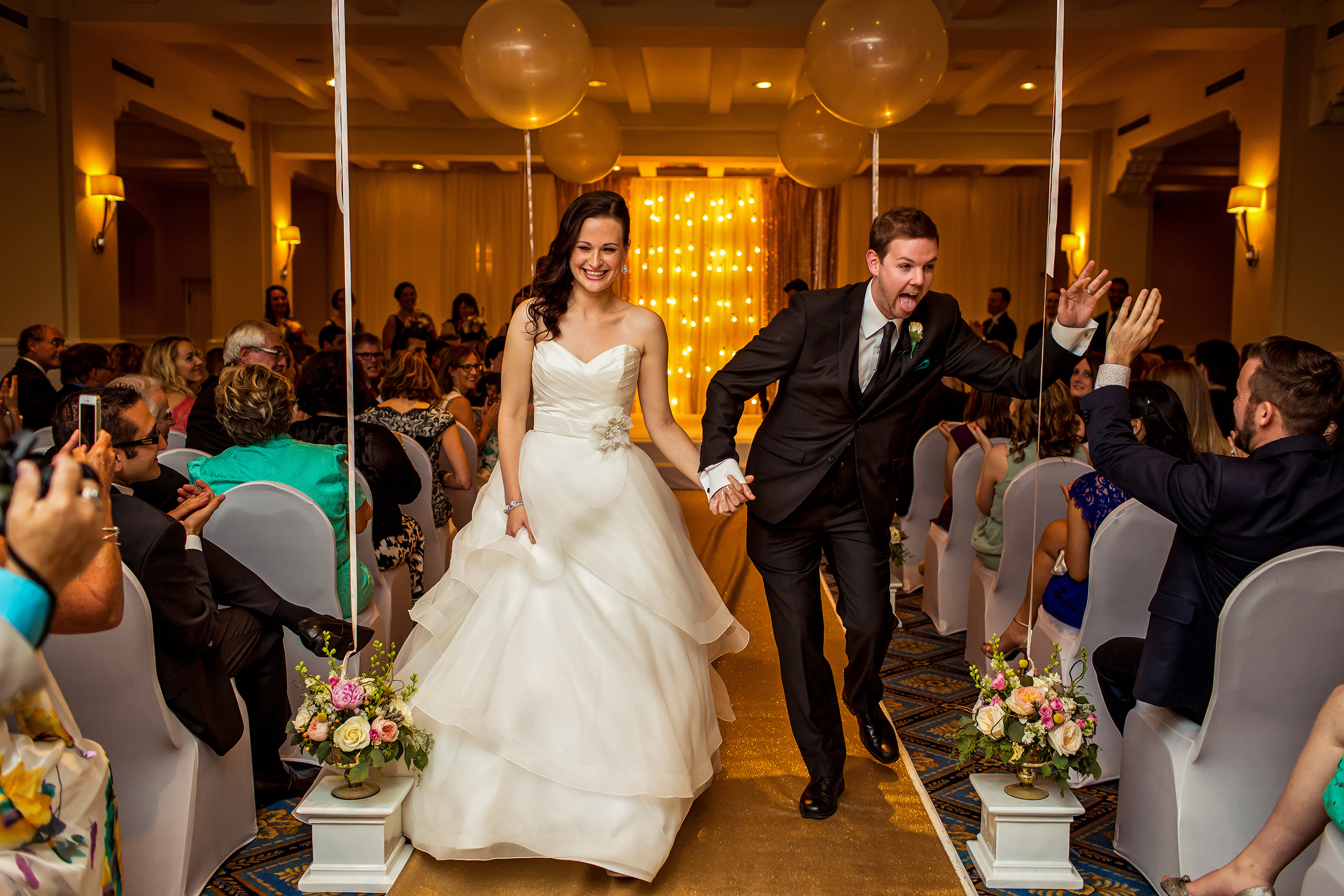 groom gives guest a high five he leaves wedding ceremony with his new wife at the chateau laurier canadian room
