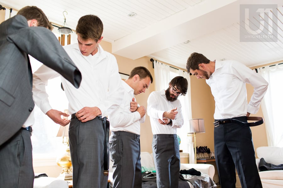 Five men standing in grey trousers and white dress shirts, getting ready for a wedding in Russell, Ontario