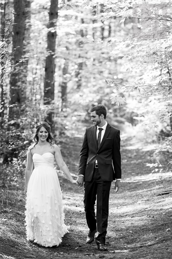 Bride and groom walking hand in hand through forested area in Russell, Ontario