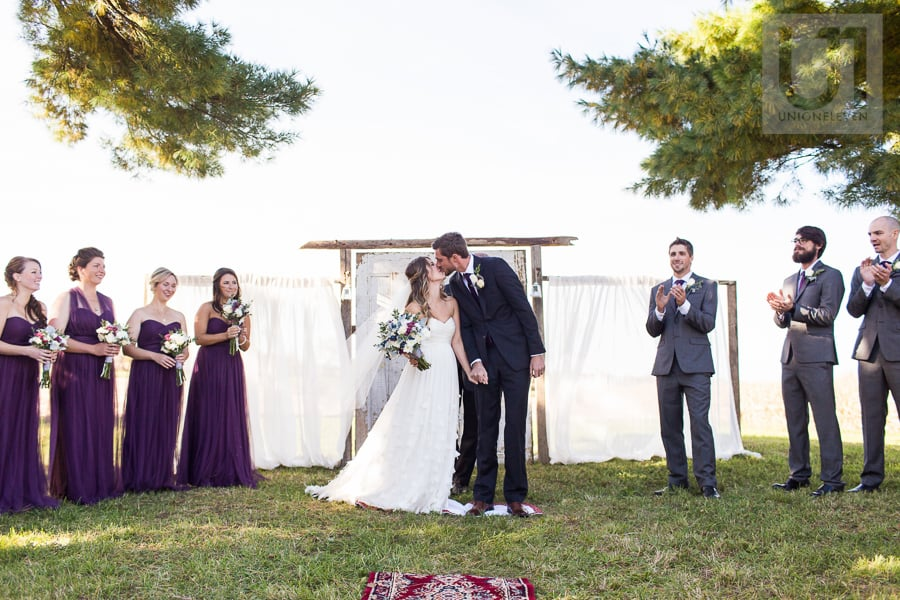 Bride and groom sharing first kiss while wedding party looks on at outdoor wedding ceremony in Russell, Ontario.
