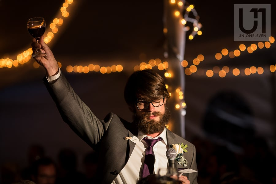 Young man holding up a wine glass as a toast during wedding reception in Russell, Ontario.