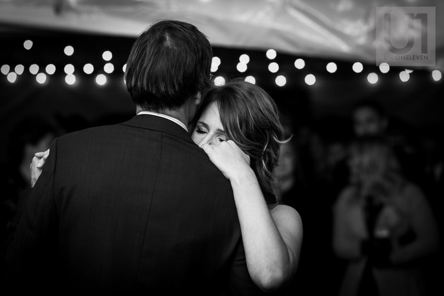 Close up of woman dancing with man under a lit up tent at wedding reception in Russell, Ontario.