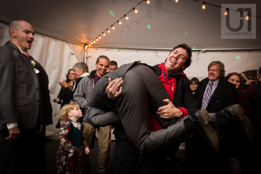 Young man carrying another man while laughing on the dance floor at wedding reception.