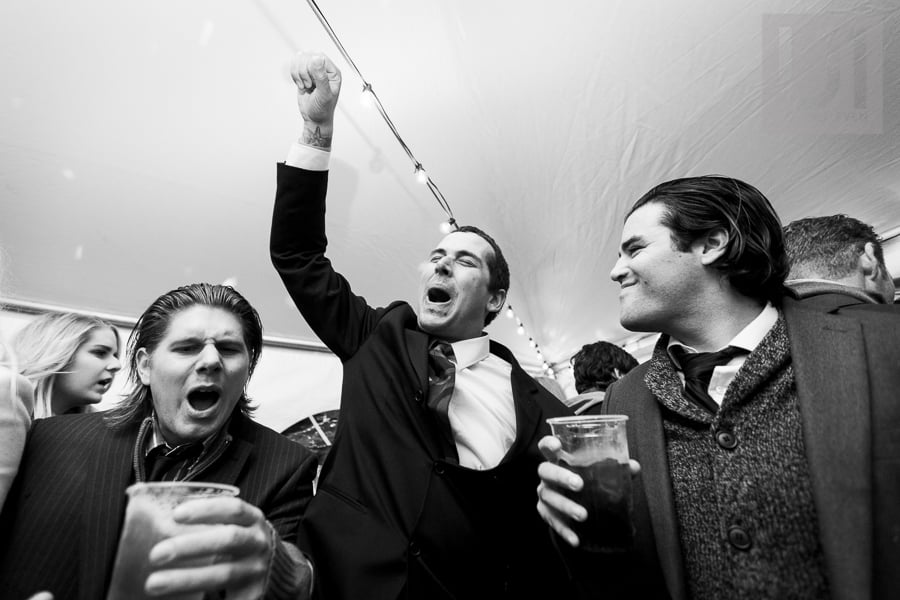 Three men dancing and cheering on dance floor at wedding reception, the man in the middle holding his fist up in the air while he appears to be singing to the music.