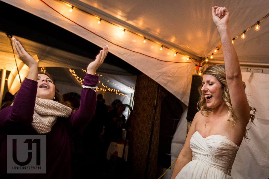 Bride dancing on dance floor at wedding reception with female guest, while holding up her fist in the air and singing to the music.