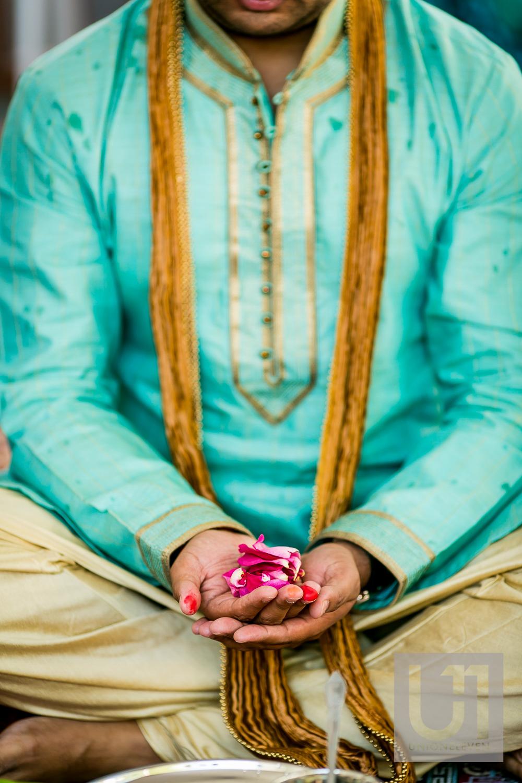 groom holding flower petals